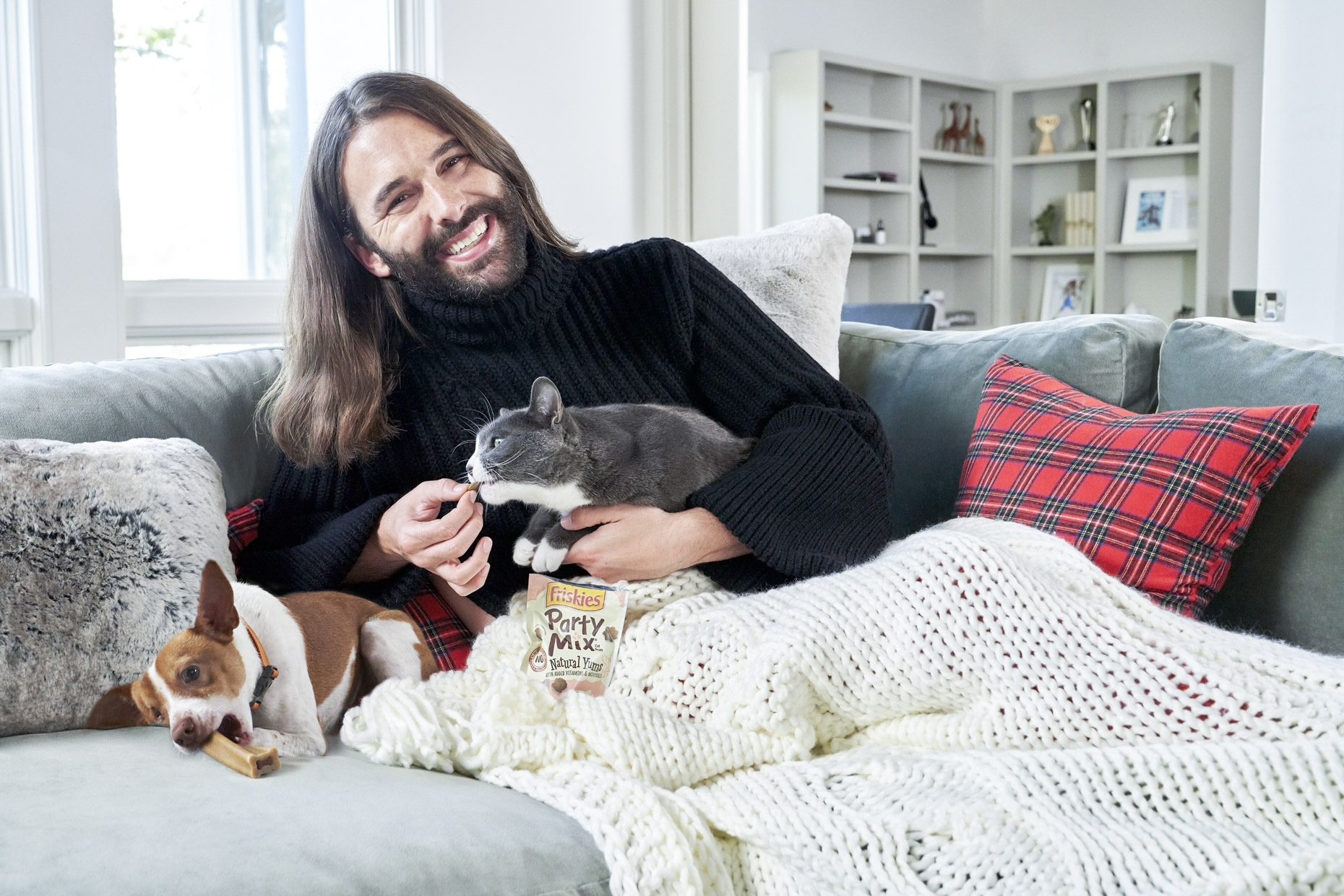 Jonathan Van Ness feeding cat Purina Friskies treat while dog chews beggin bone on couch