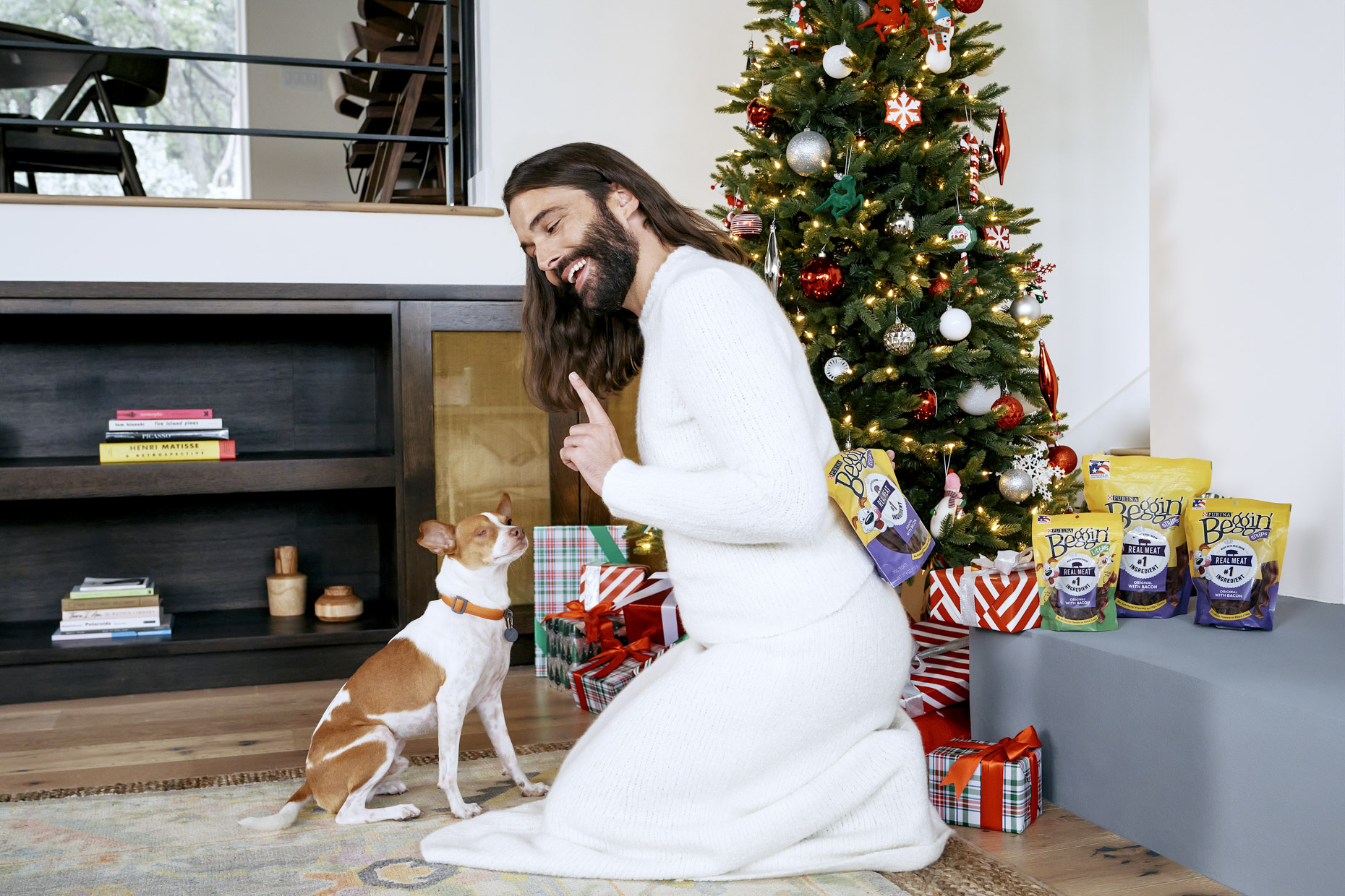 Jonathan Van Ness giving pet dog Pablo Purina Beggin treat in front of Christmas tree