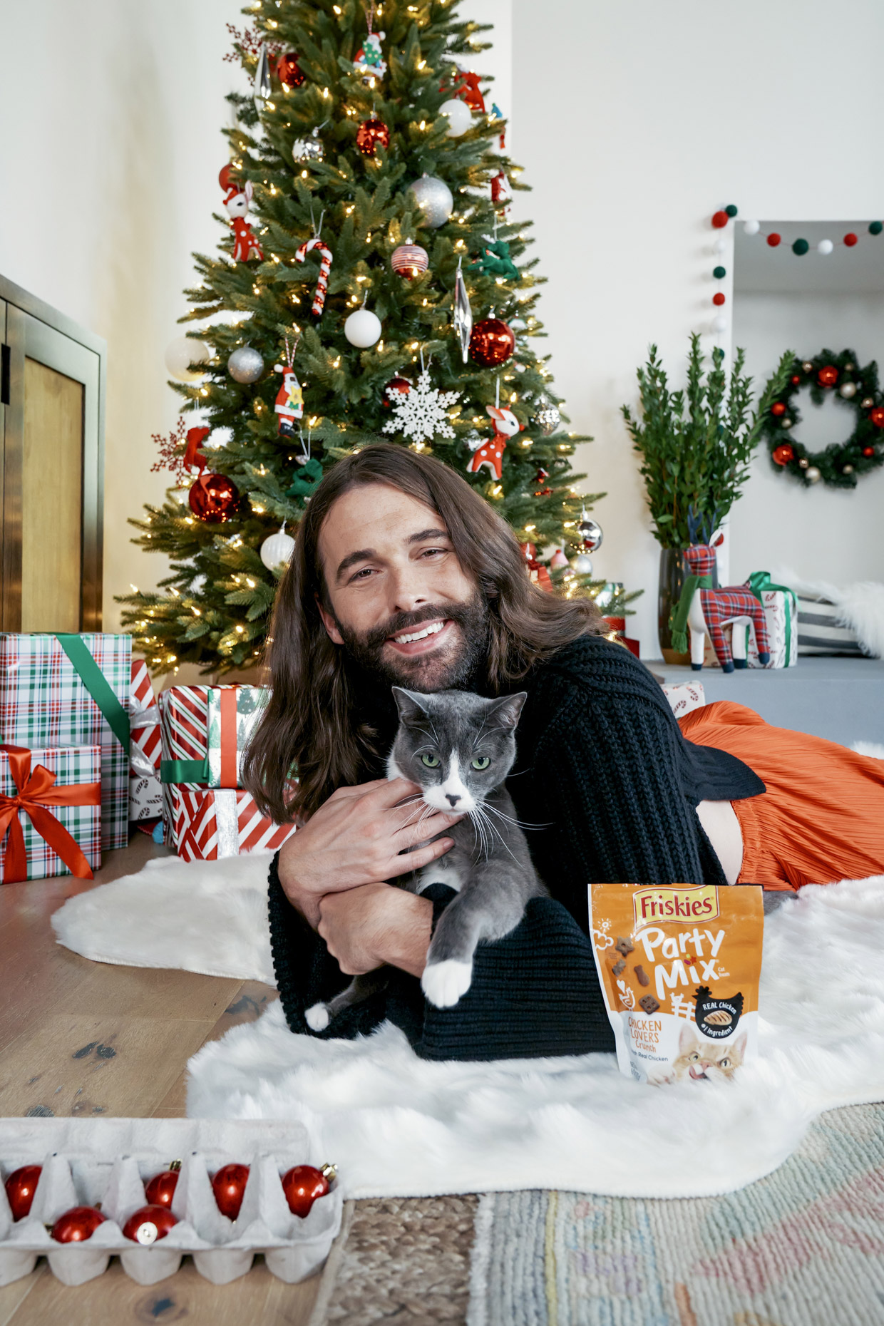 Jonathan Van Ness snuggling cat in front of Christmas tree with Friskies party mix