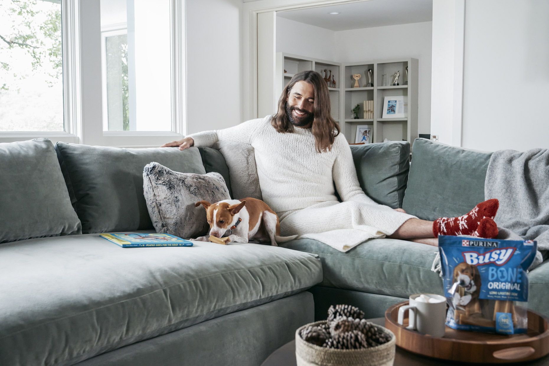 Jonathan Van Ness watching pet dog Pablo on couch with Purina Busy Bone treat