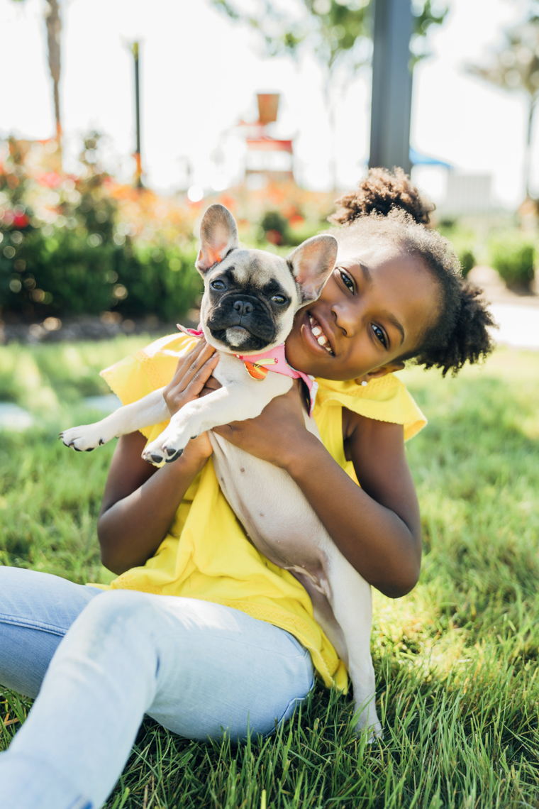 Smiling black girl in yellow shirt hugging Frenchie puppy in yard. Kids lifestyle photo by Inti St Clair Austin Texas
