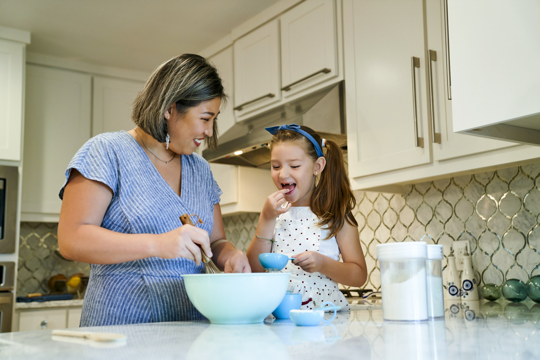 Korean girl baking cookies with her mom in home kitchen