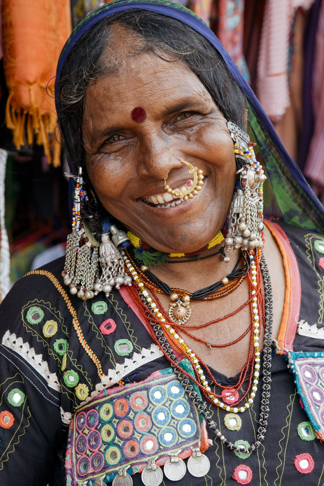 Inti St Clair photo of woman with bright clothes and bold jewelry laughing in Goa India