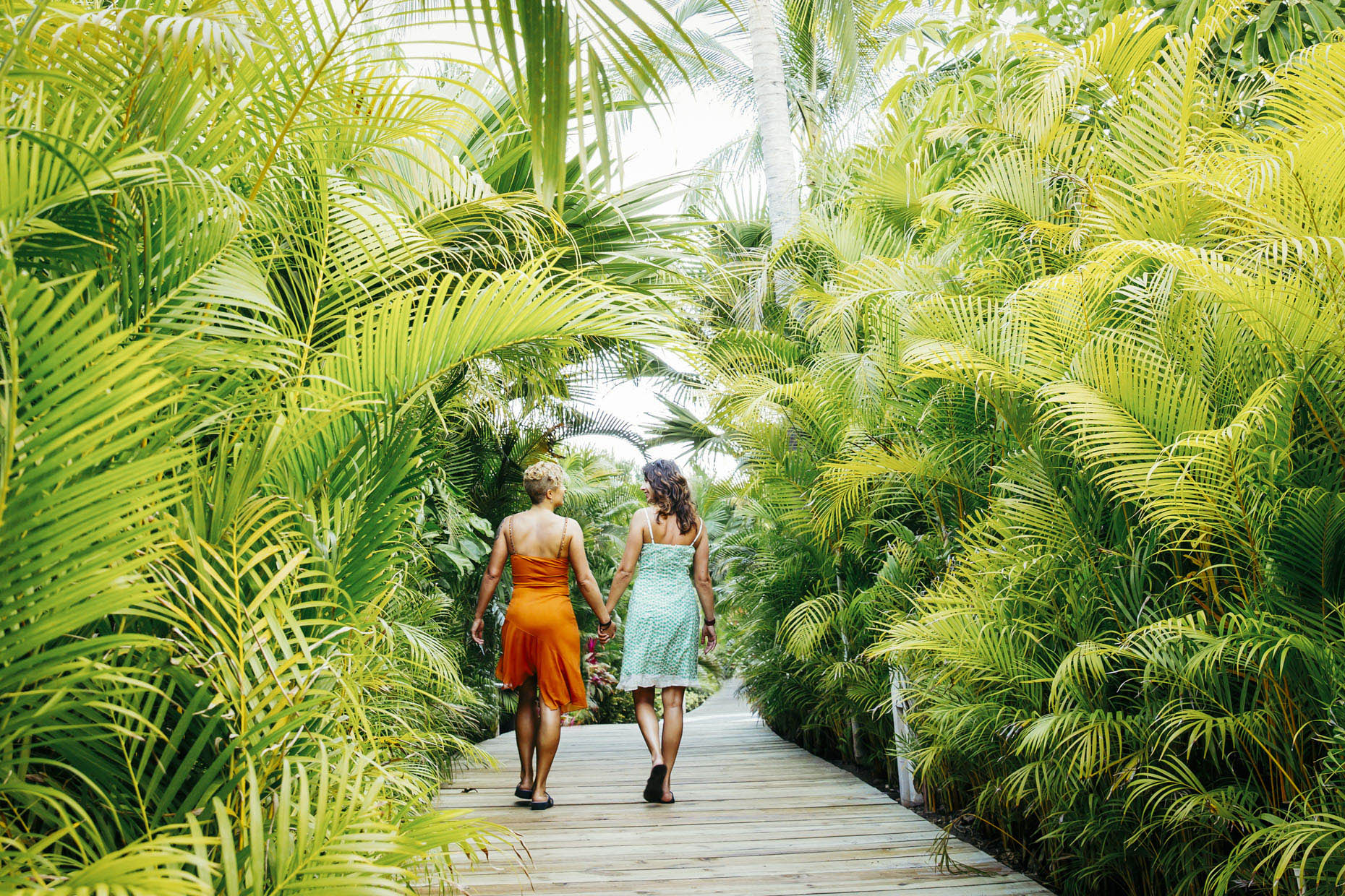 Lesbian-couple-walking-holding-hands-on-path-in-tropics-Mexico-Inti-St-Clair-is201404130602