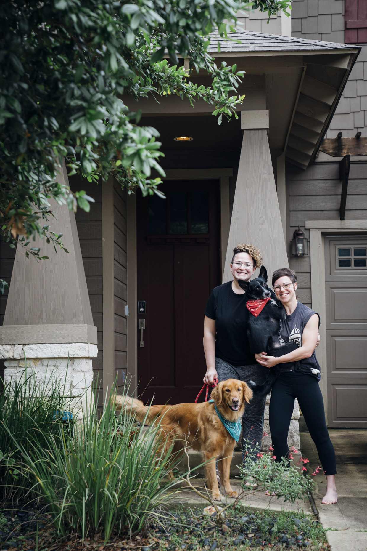 Lesbian couple with dogs in front of house