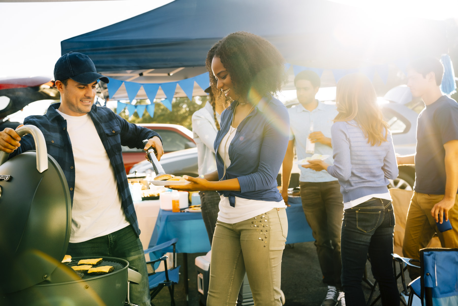 Man giving woman hamburger from grill at tailgate party
