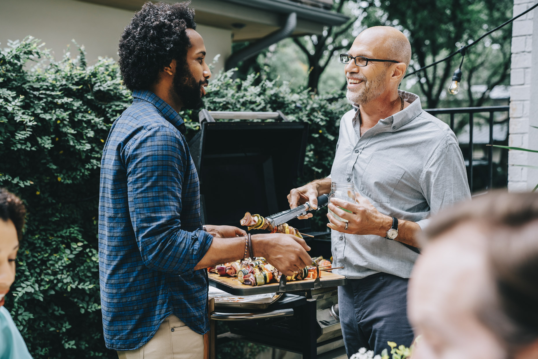 Man holding tray while friend puts food from grill on it