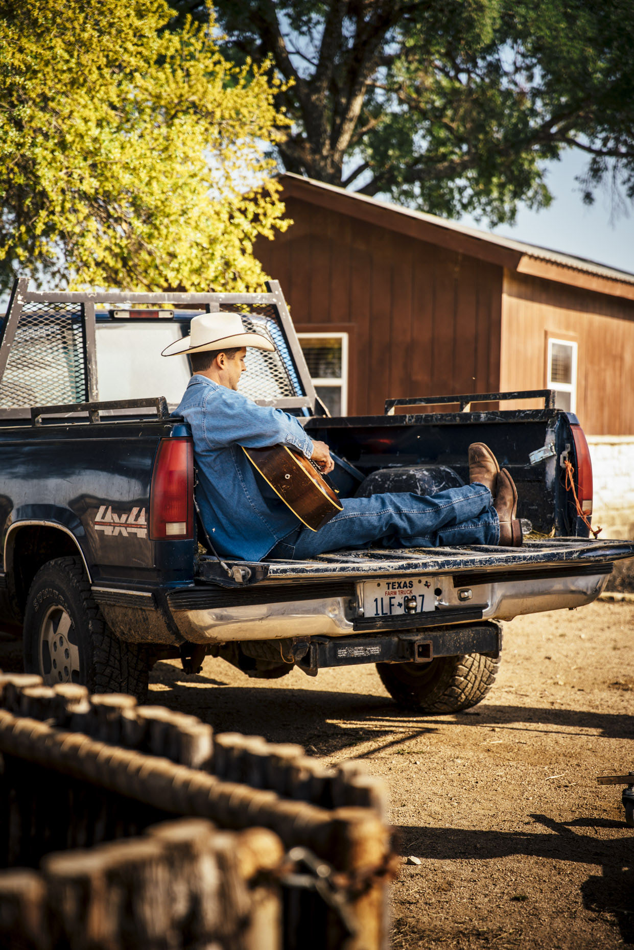 Man in cowboy hat sitting in back of pickup truck on horse ranch playing guitar