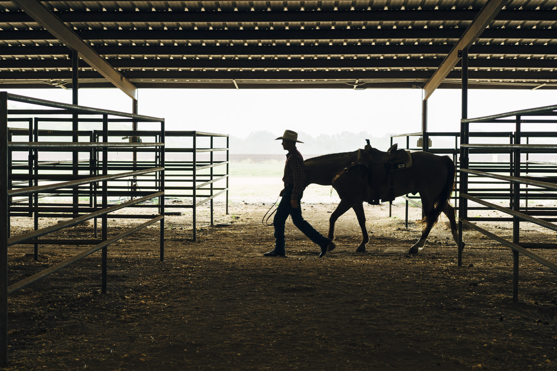 Silhouette of man in cowboy hat walking with horse through stable
