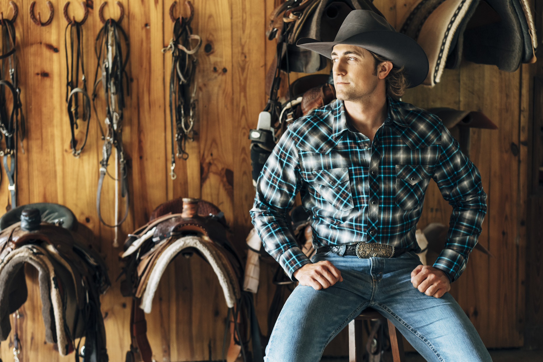 Man in cowboy hat wearing wrangler jeans and shirt sitting in front of saddles in horse barn