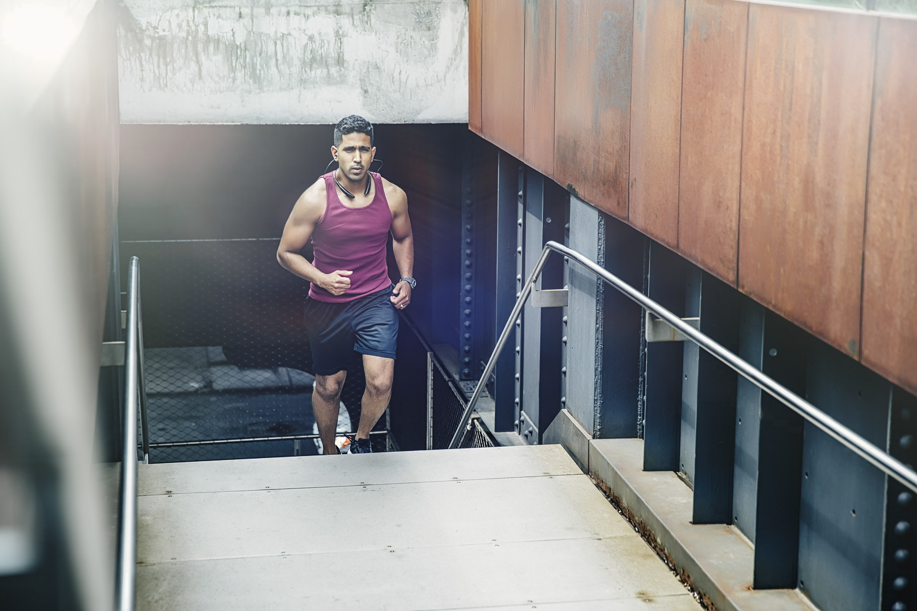 Man in maroon tank top and wireless headphones running up stairs