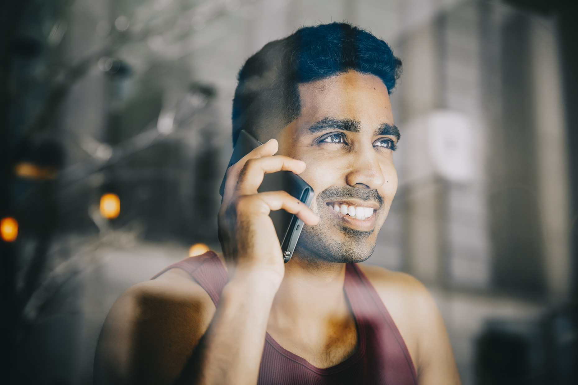 Man in maroon tank top talking on cell phone looking out window