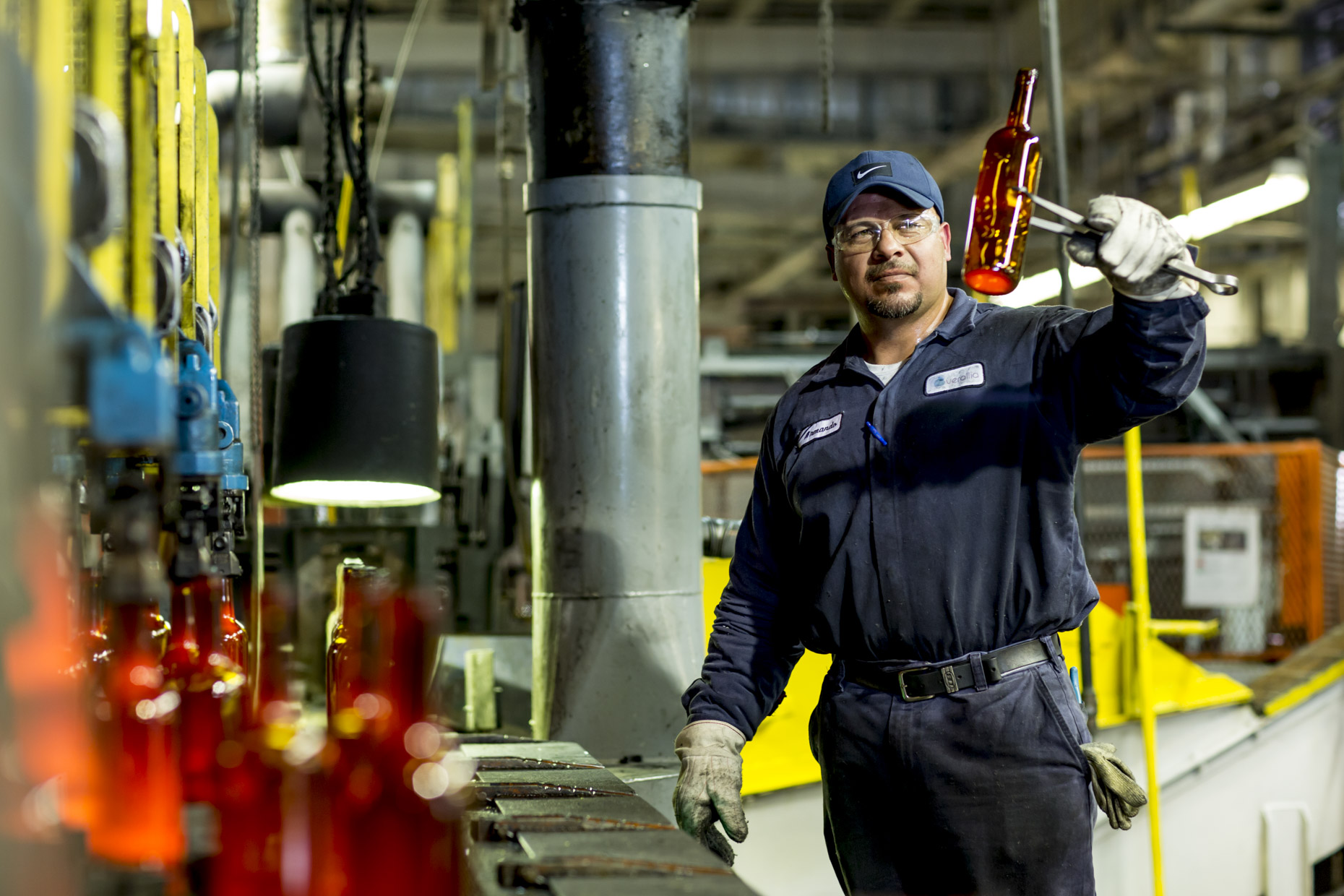 Man-inspecting-molton-glass-wine-bottle-in-factory-Inti-St-Clair-is201206190674
