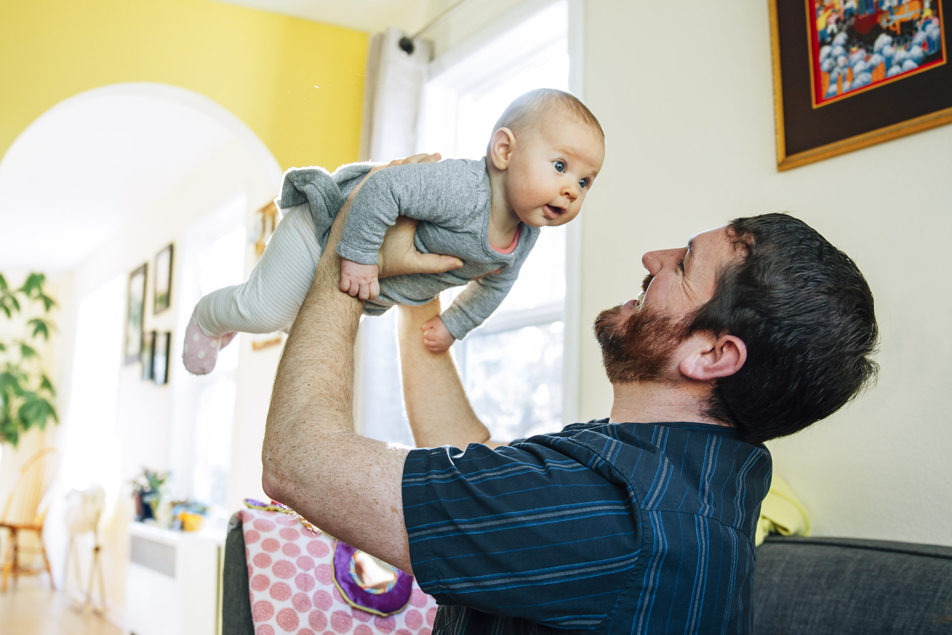 Man lifting baby into air in home