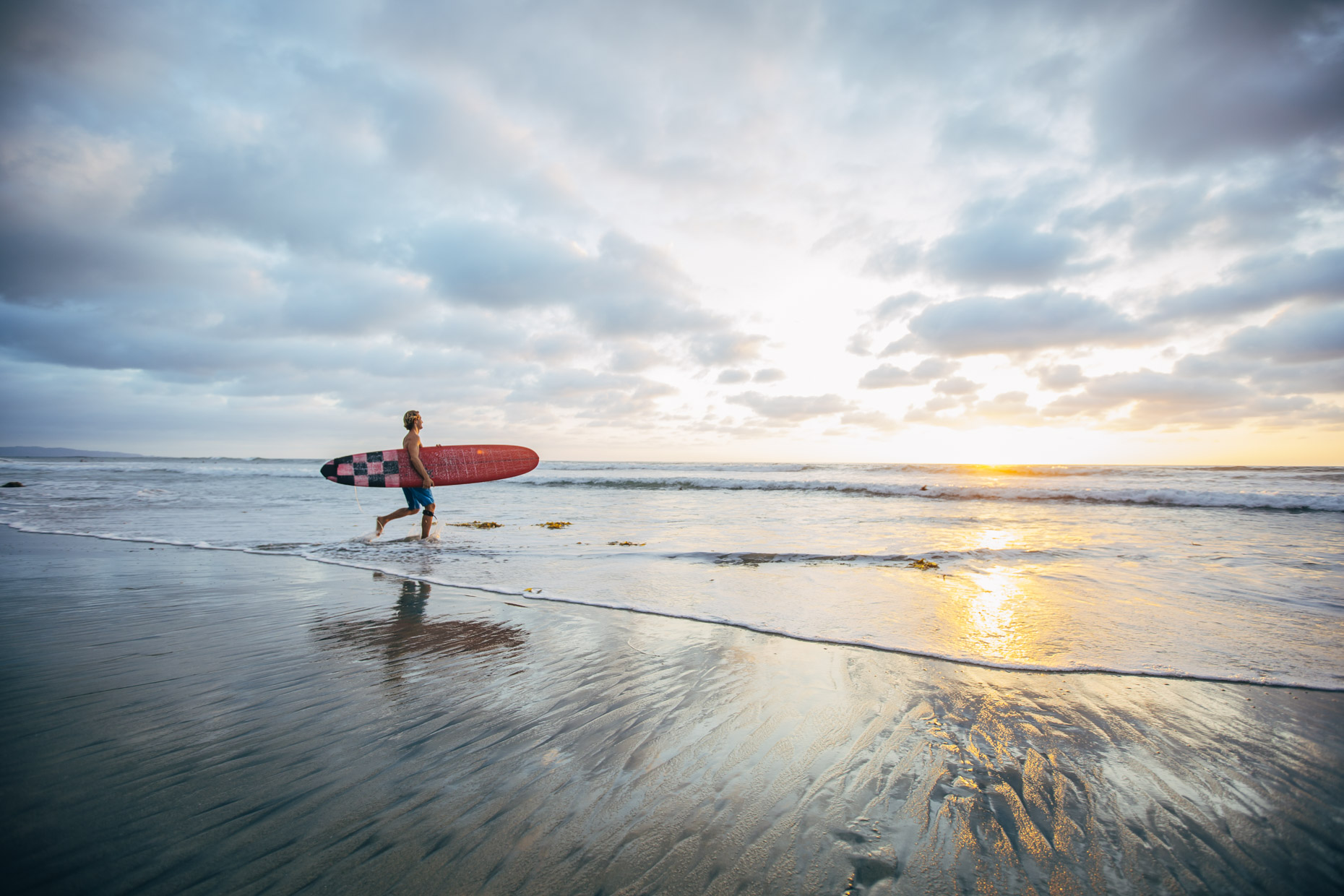 Man with surfboard running into ocean on beach at sunset