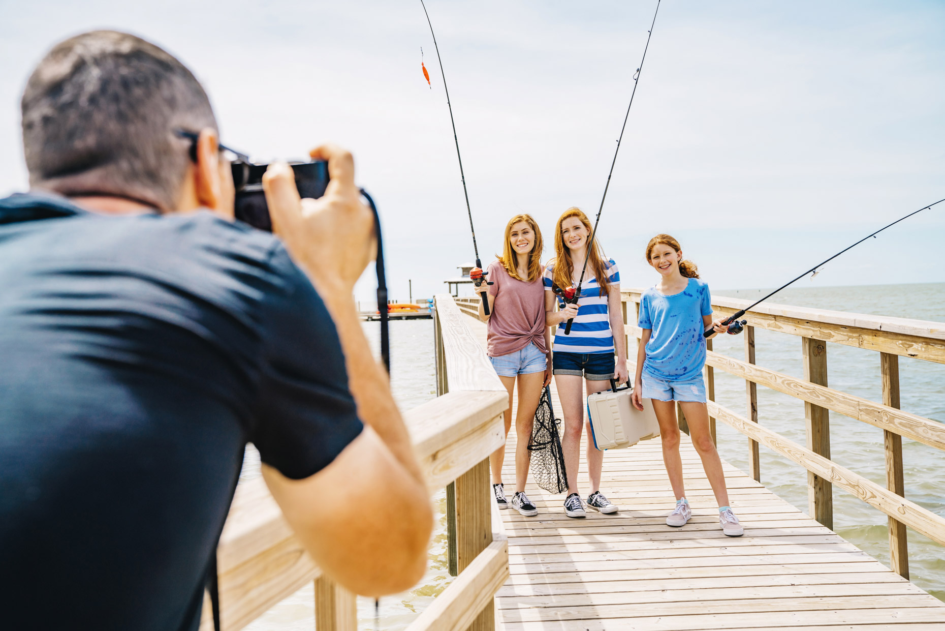 Man taking photo of girls on fishing dock