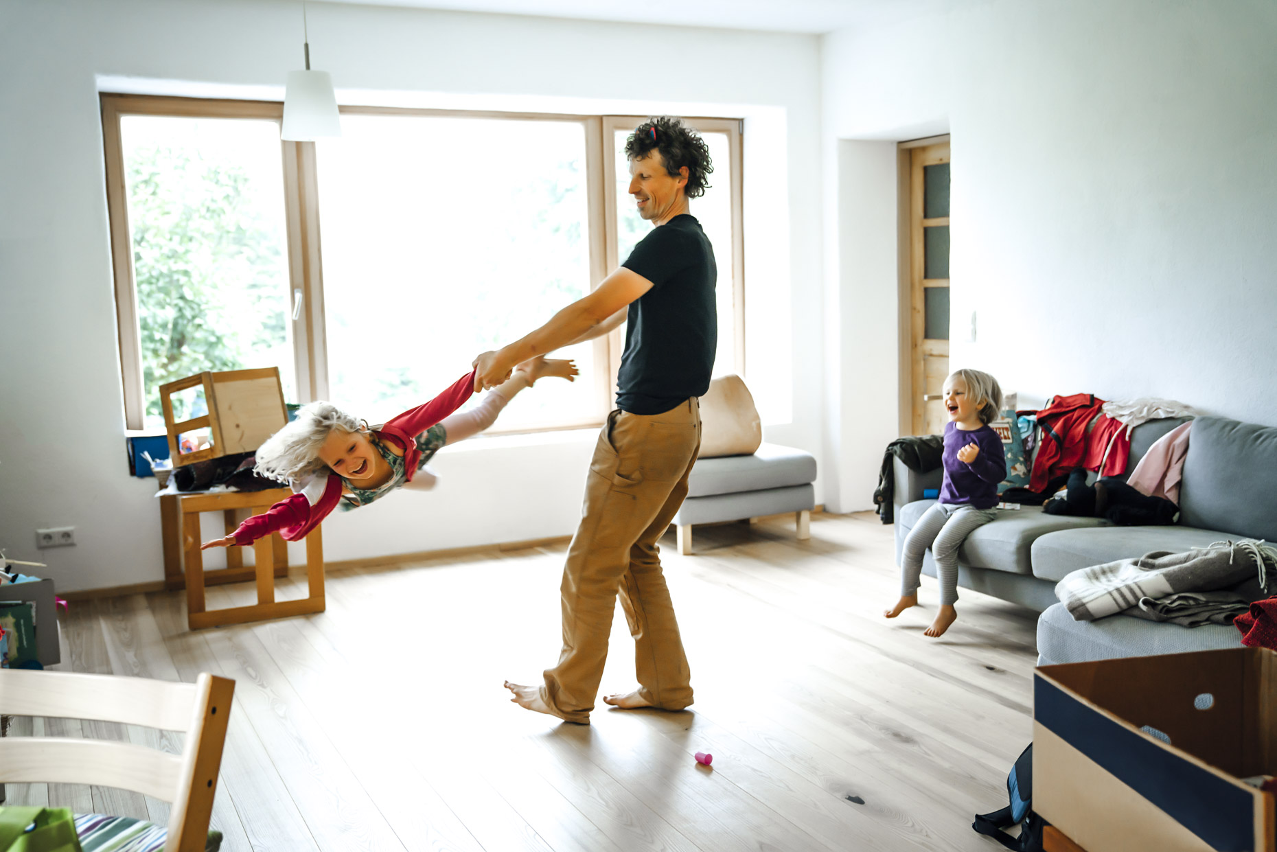 Man twirling happy daughter around messy living room