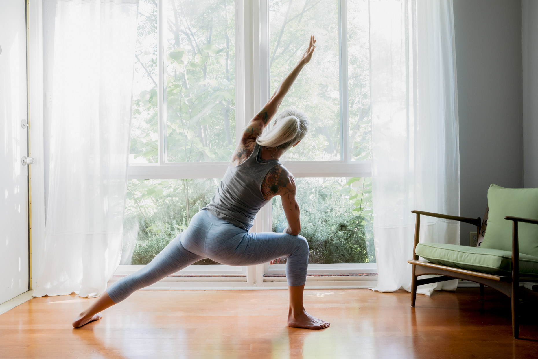 Inti St Clair photo of mature woman with grey hair practicing yoga in living room of home