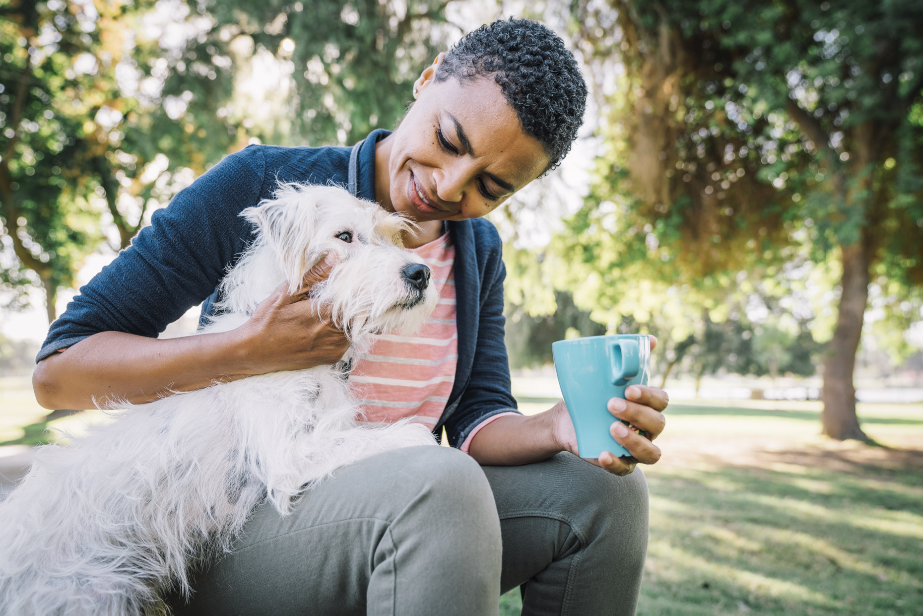 Mature woman sitting outside drinking coffee and hugging terrier dog