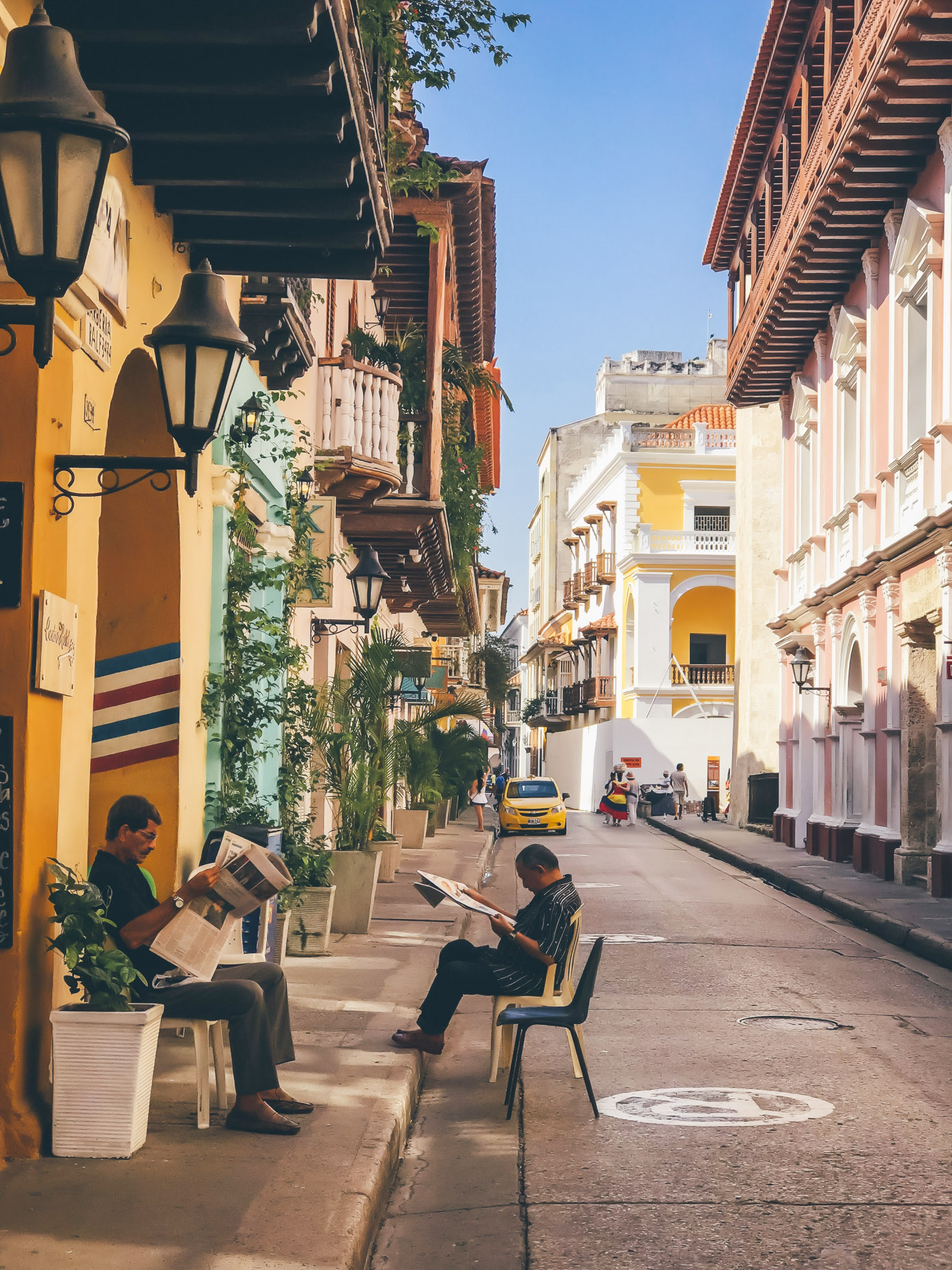 Old men sitting on sidewalk in Cartagena Colombia reading newspapers