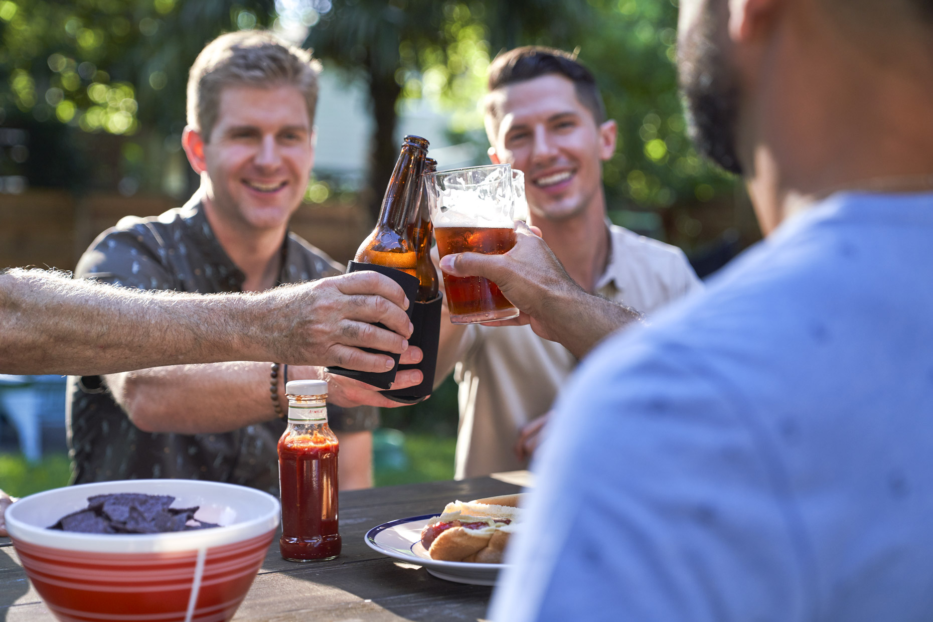Men toasting beer at backyard bbq