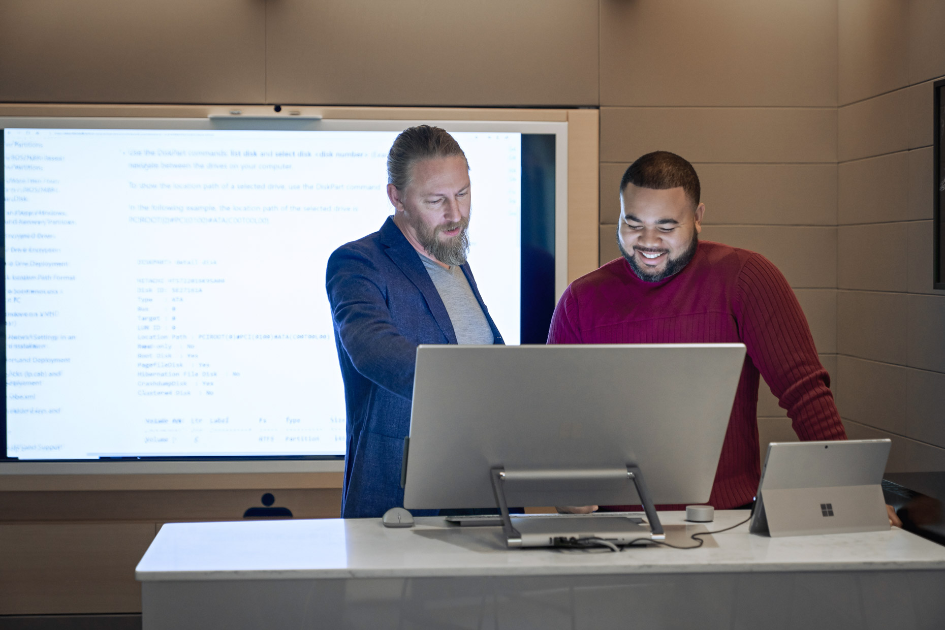 Men working together at computer with screen behind them
