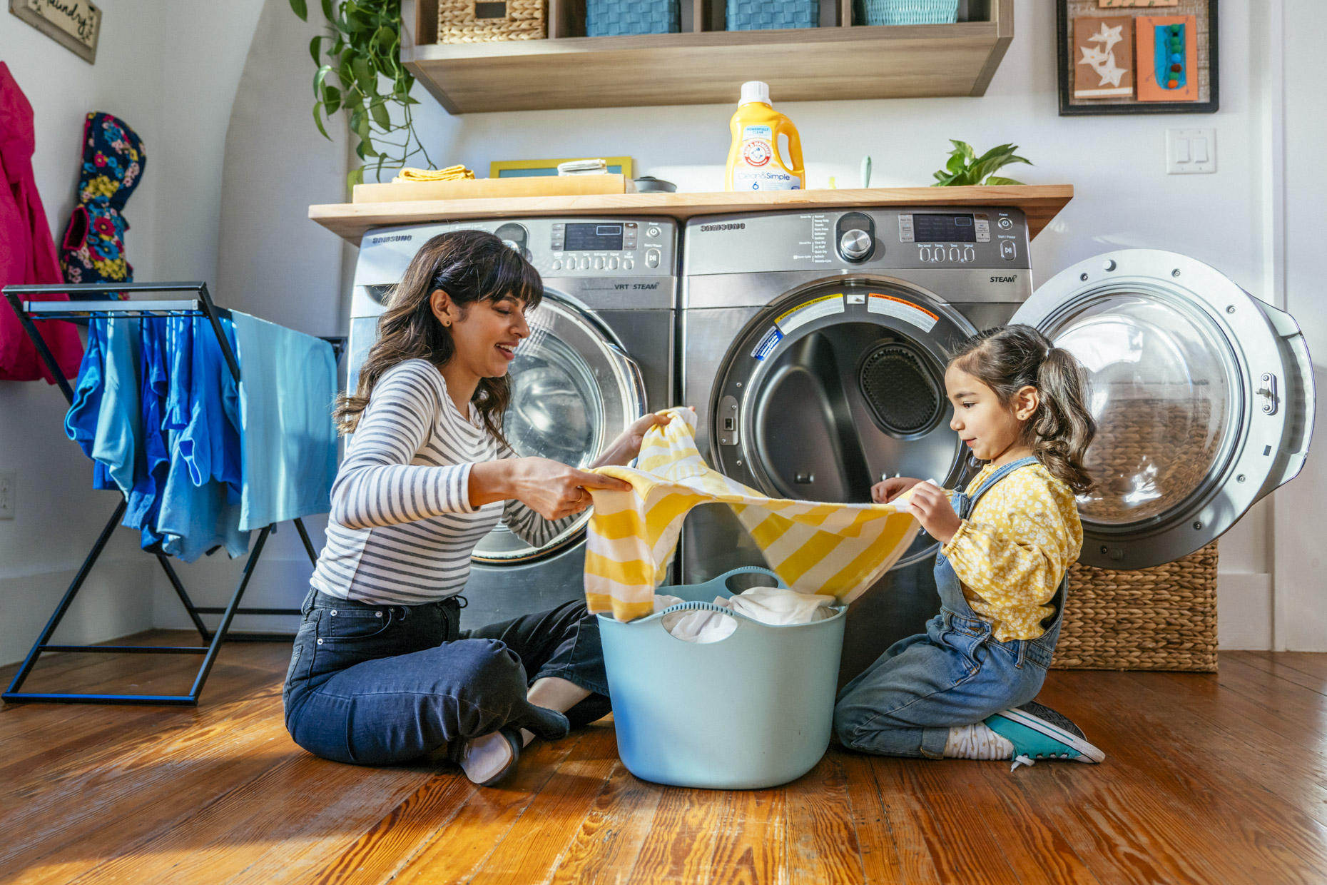Mom and daughter folding laundry together on floor by dryer