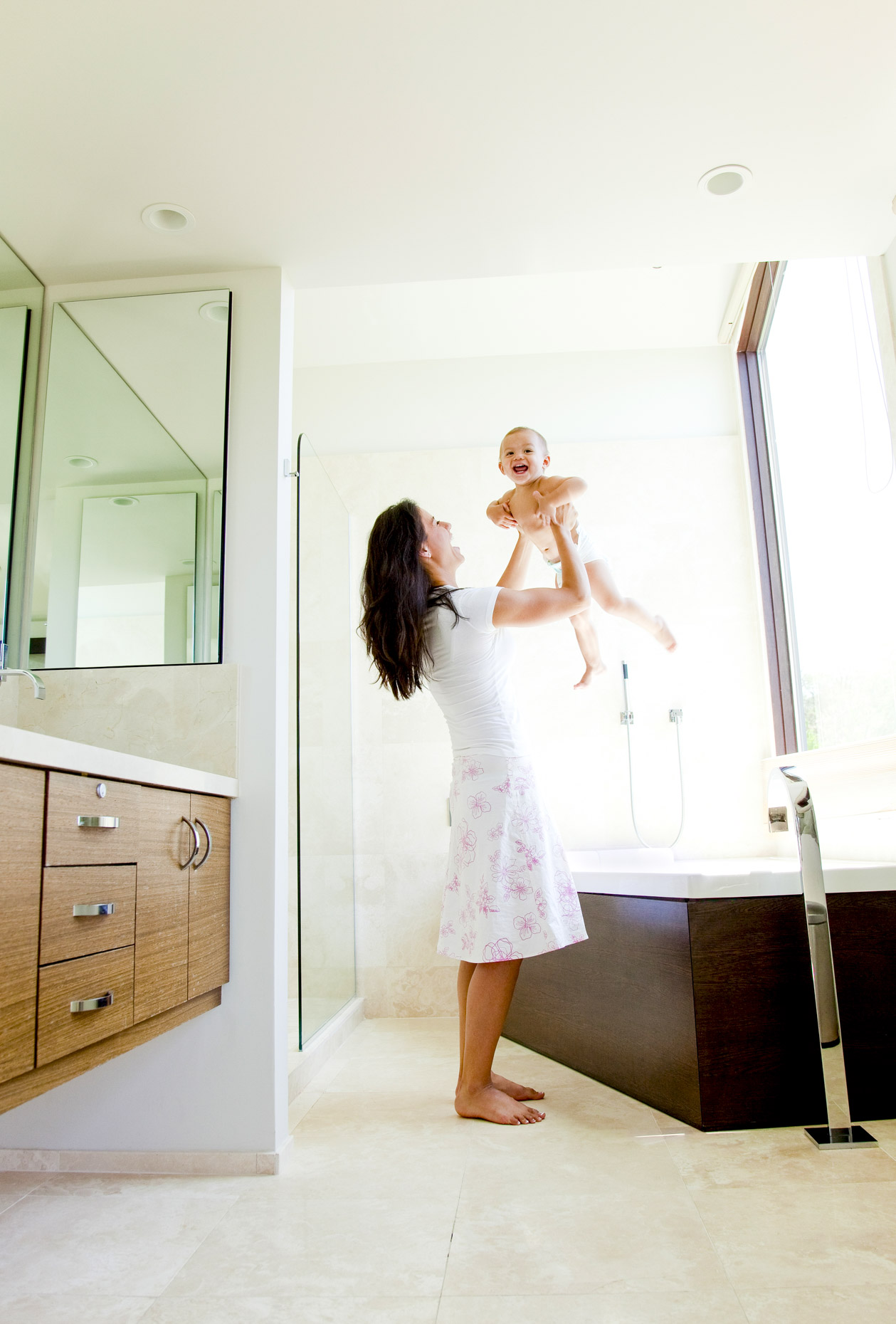 Mom lifting smiling baby overhead in bathroom