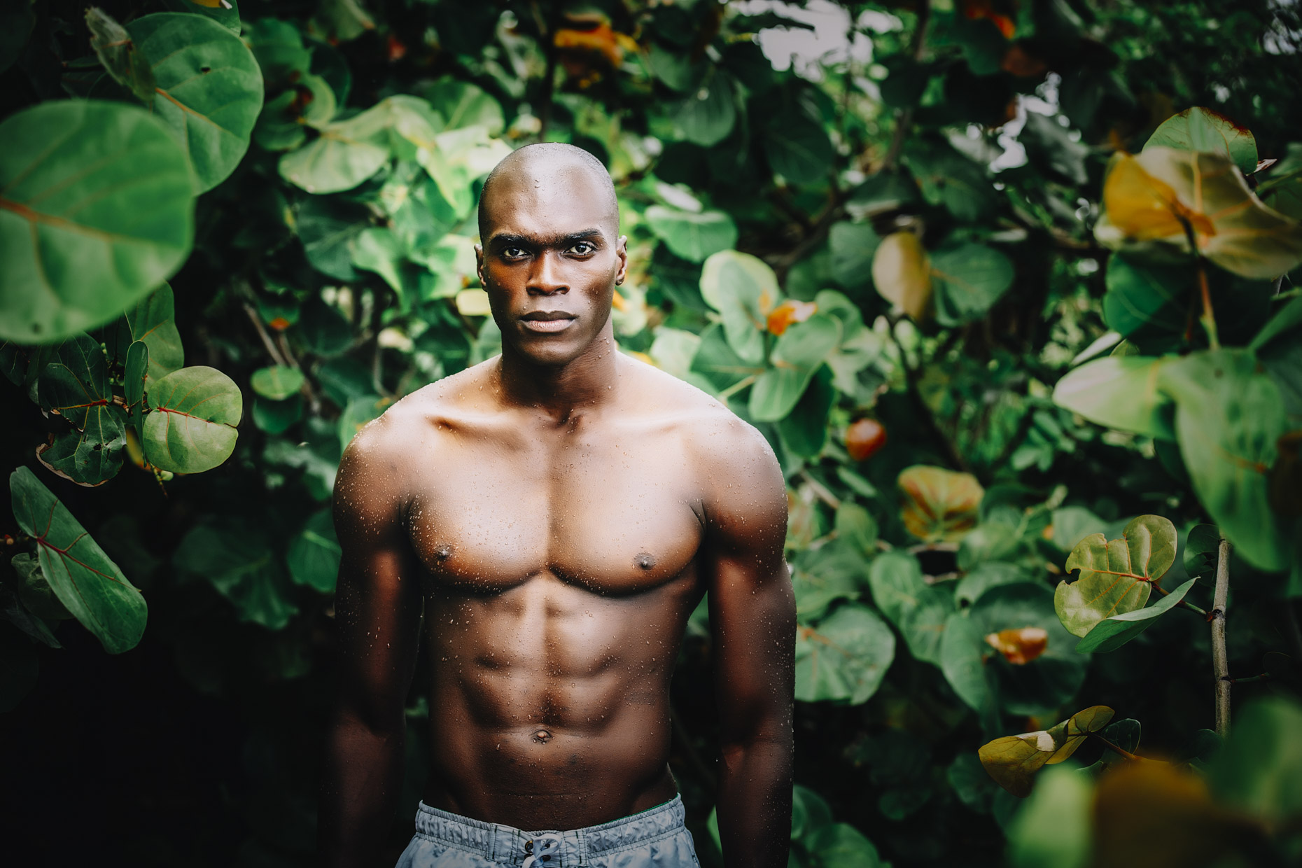 Portrait of muscled fit black bald shirtless man standing in tropical forest
