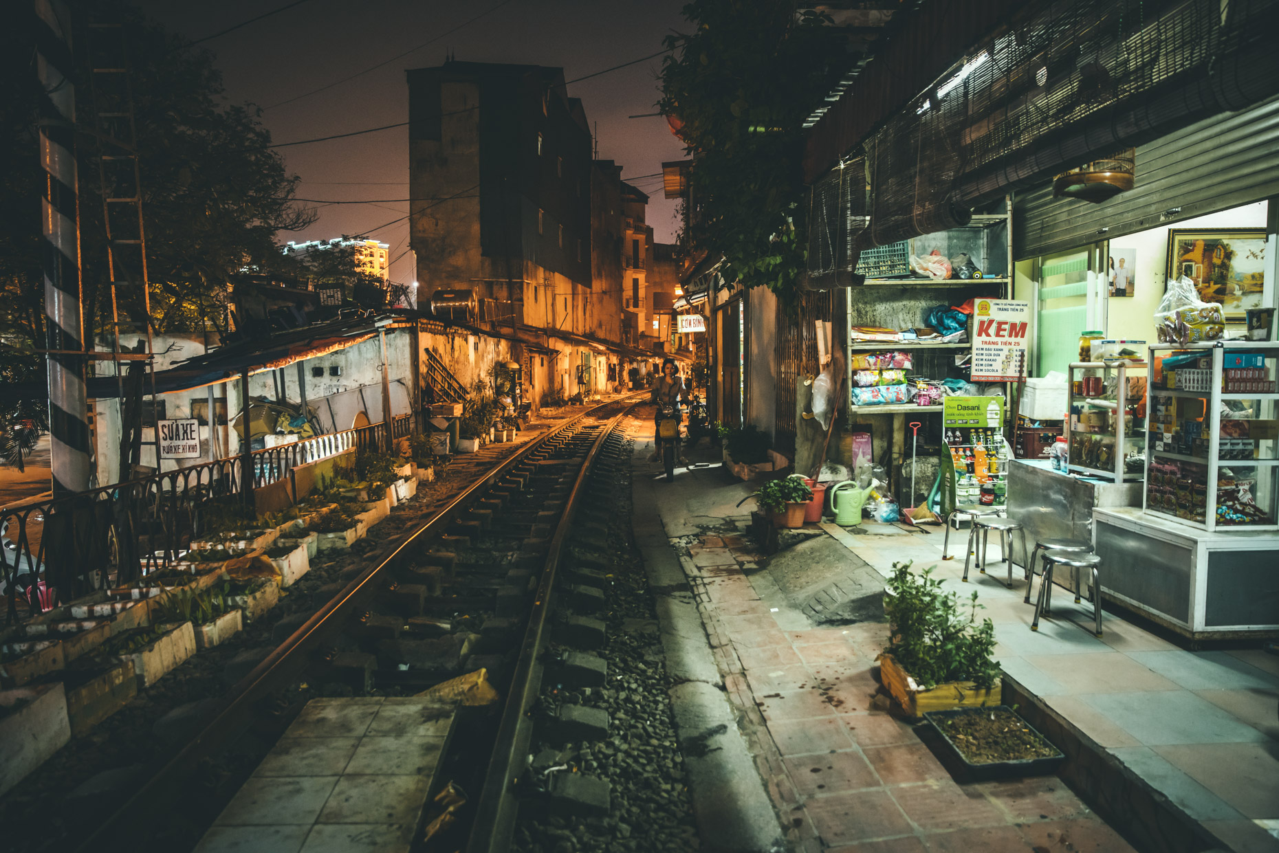 Nightscape of railroad tracks next to grocery store in Hanoi, Vietnam