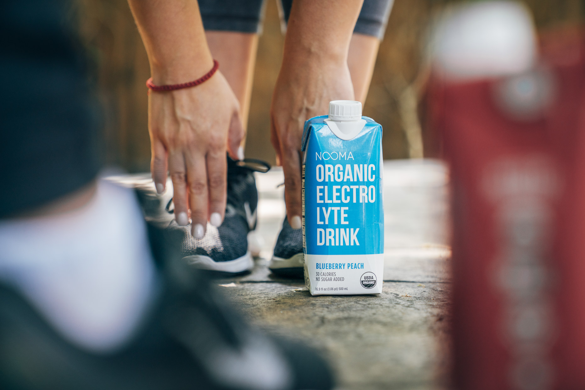 Woman stretching touching toes next to Nooma electrolyte drink