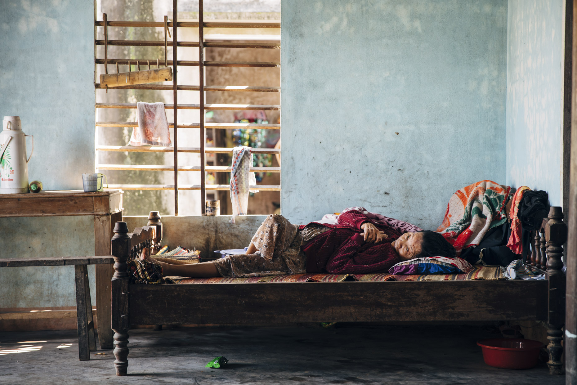 Old Woman in colorful clothes laying on wooden bed in Vietnam