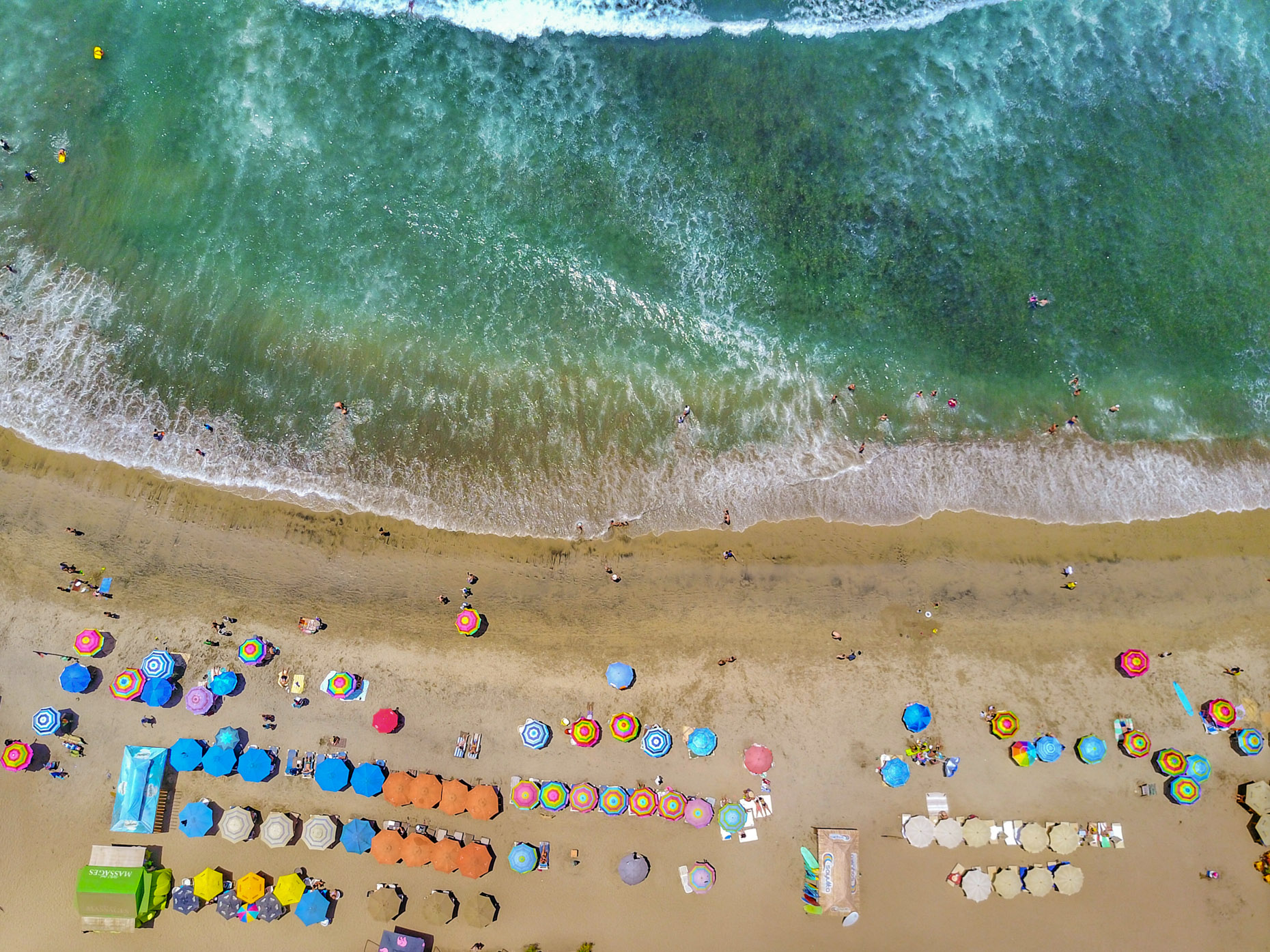 Overhead view of beach with colorful umbrellas