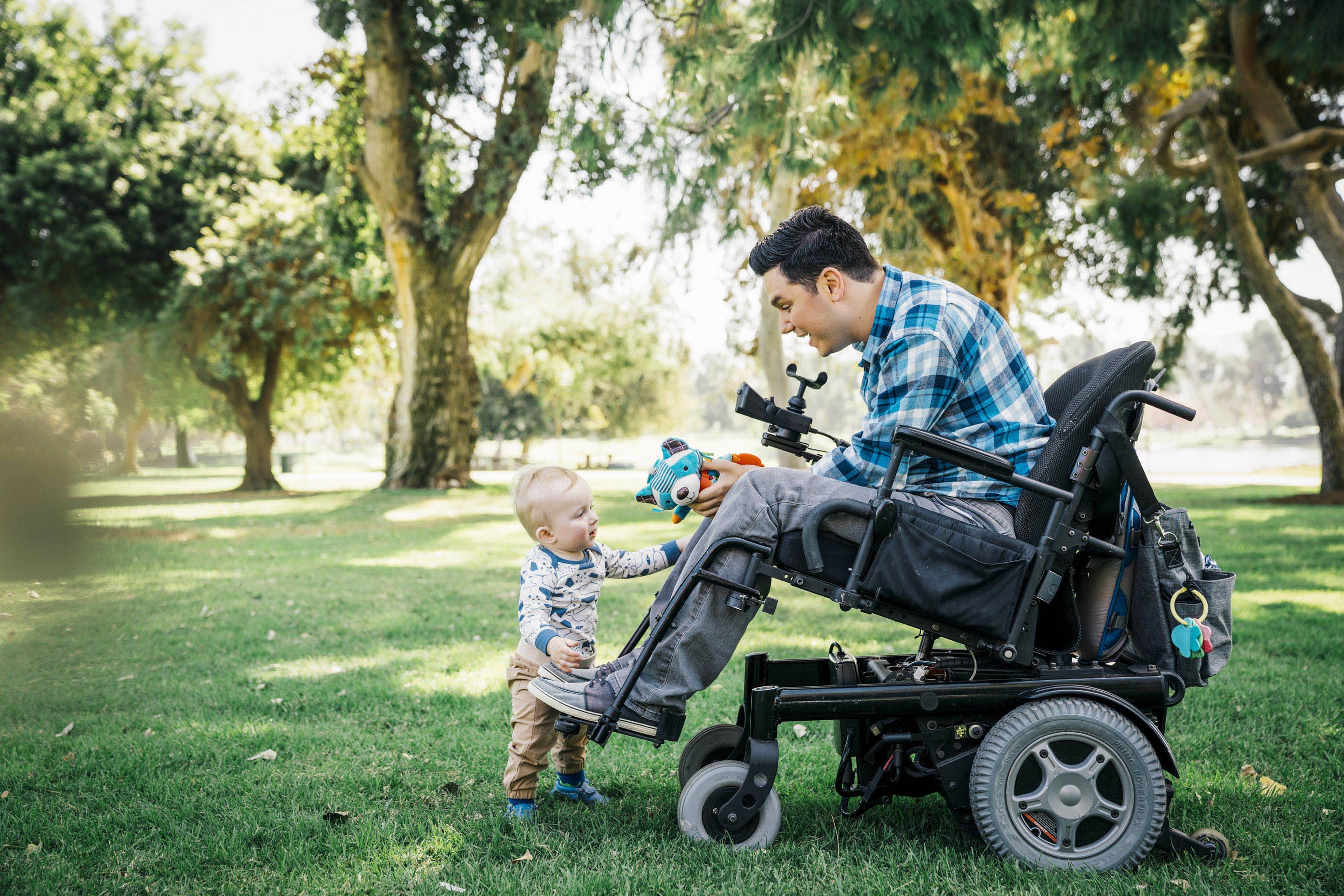 Inti St Clair photo of paraplegic man in wheel chair playing with toddler son in park