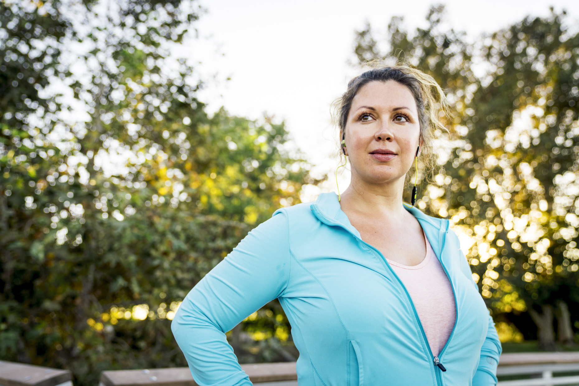 Plus-sized woman in fitness attire looking off in to distance