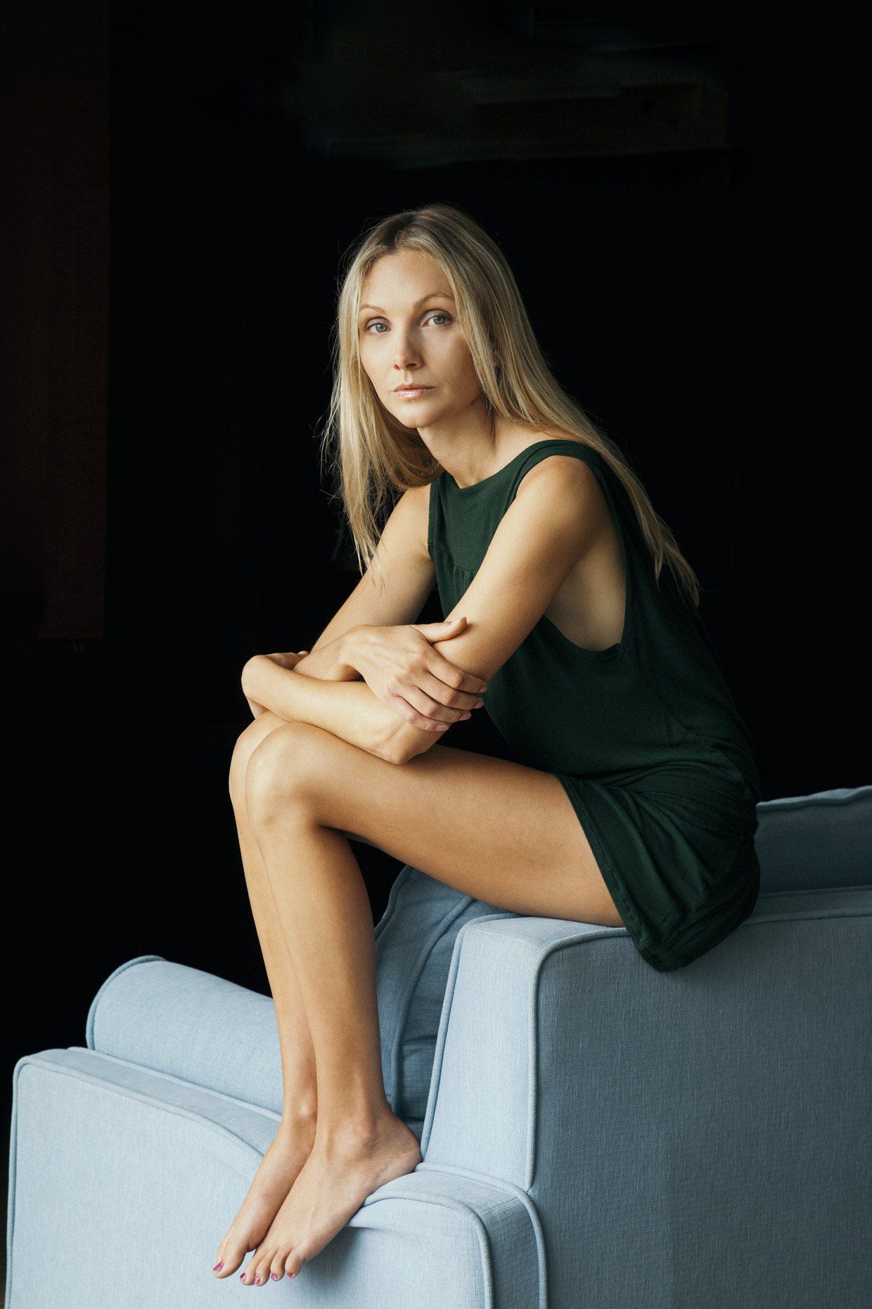 Portrait of blonde woman sitting on edge of couch