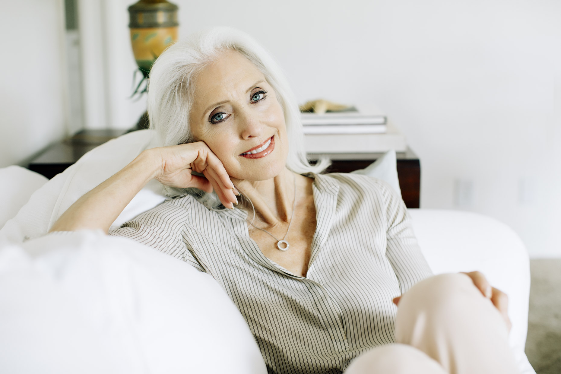 Beautiful mature silver haired woman relaxing on couch