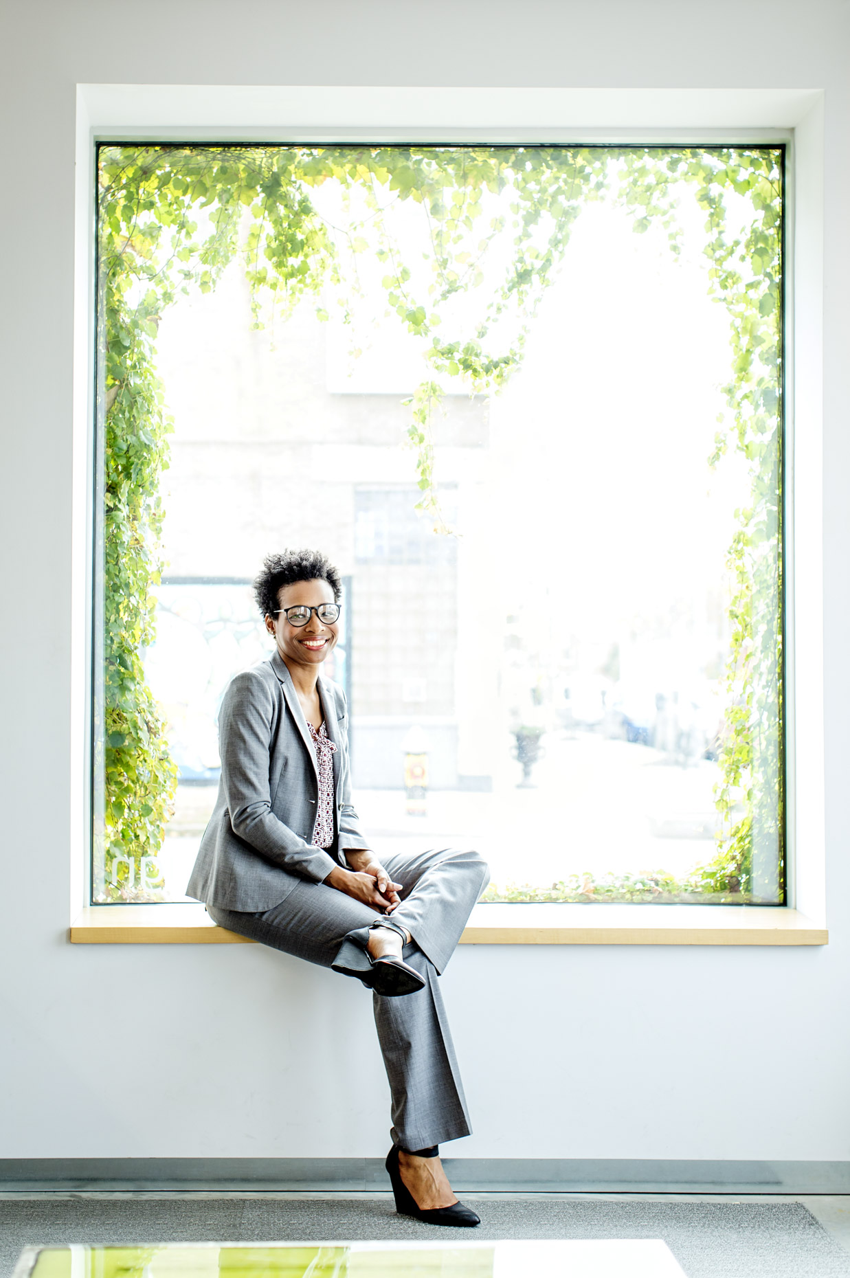 Portrait of black business woman in suit sitting in office window