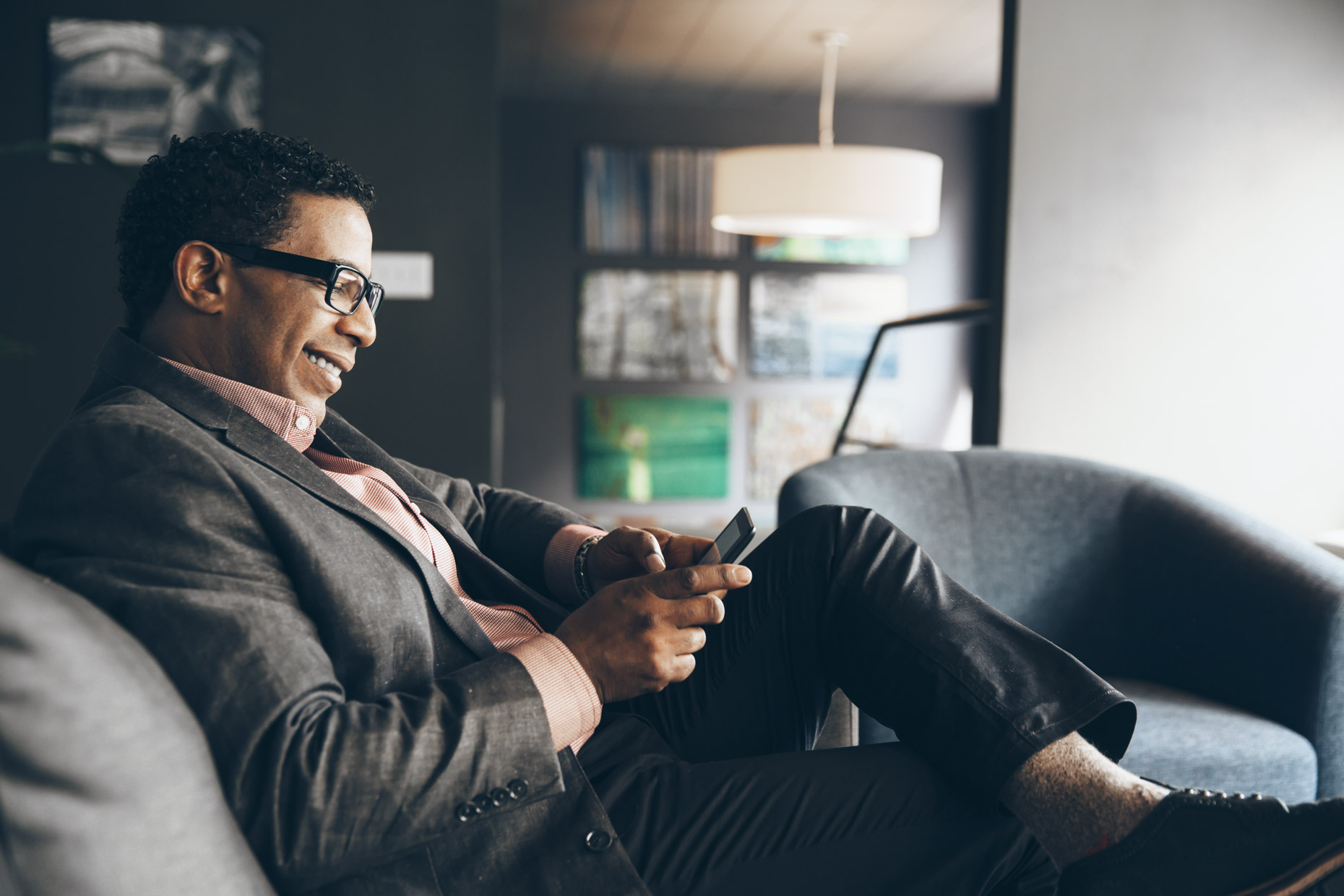 Portrait of smiling business man sitting and texting on phone