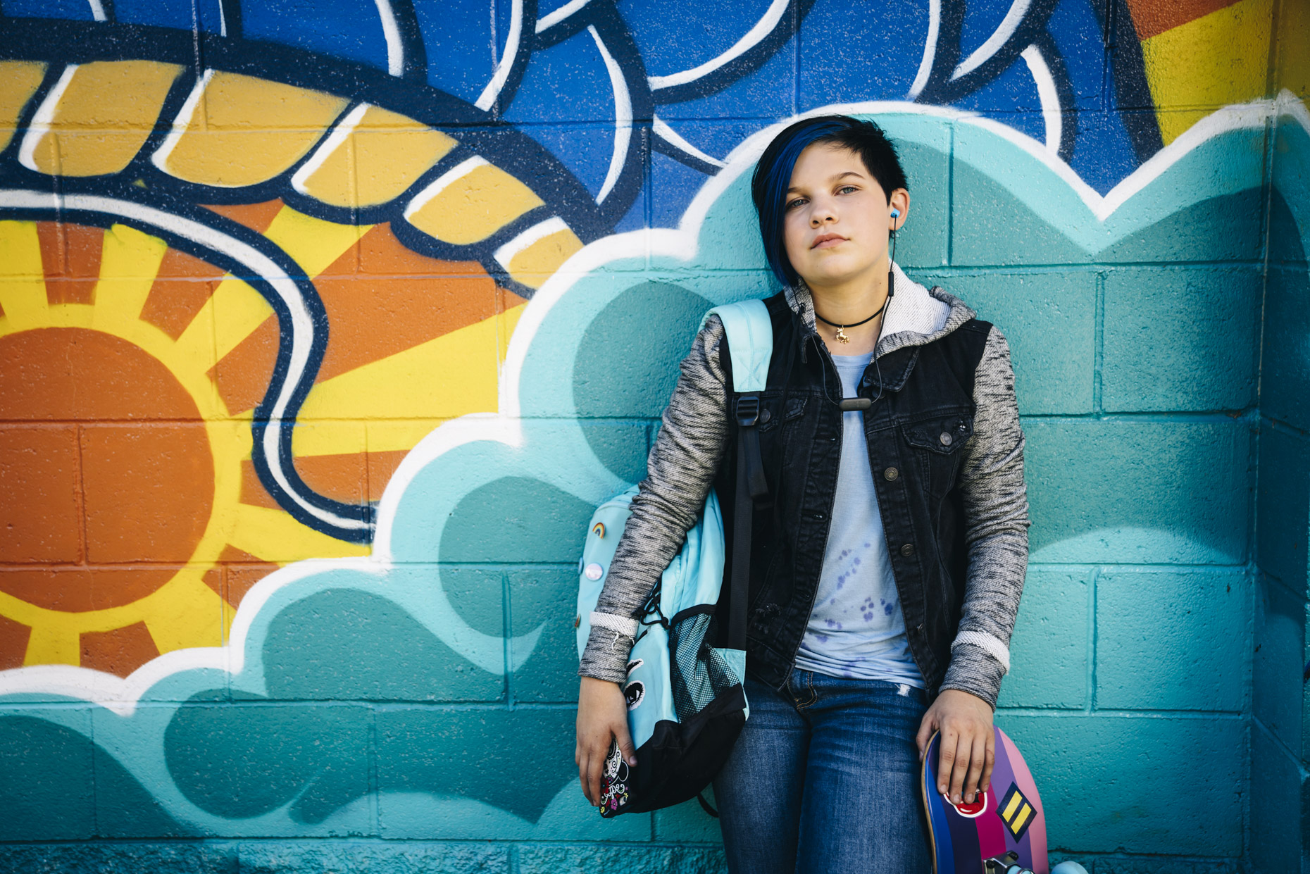 Portrait of transgender teen leaning on colorful grafitti wall