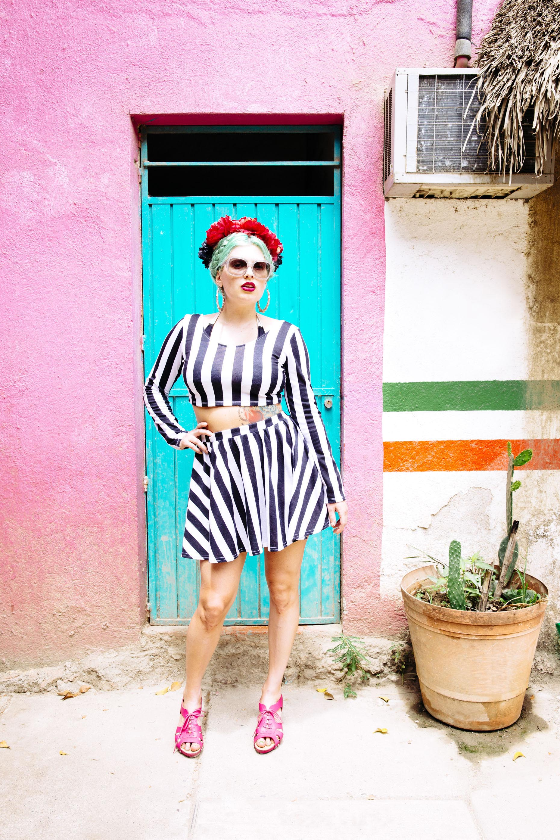 Portrait-woman-black-white-striped-dress-flowers-pinkwall-blue-door-Inti-St-Clair-is201404090189