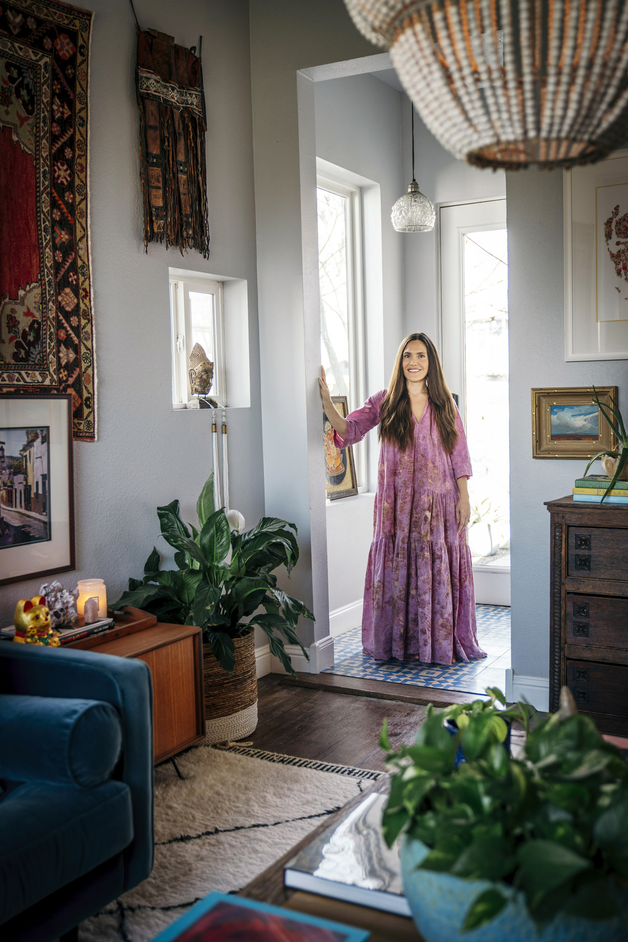 Portrait of woman in long pink dress in art-filled home