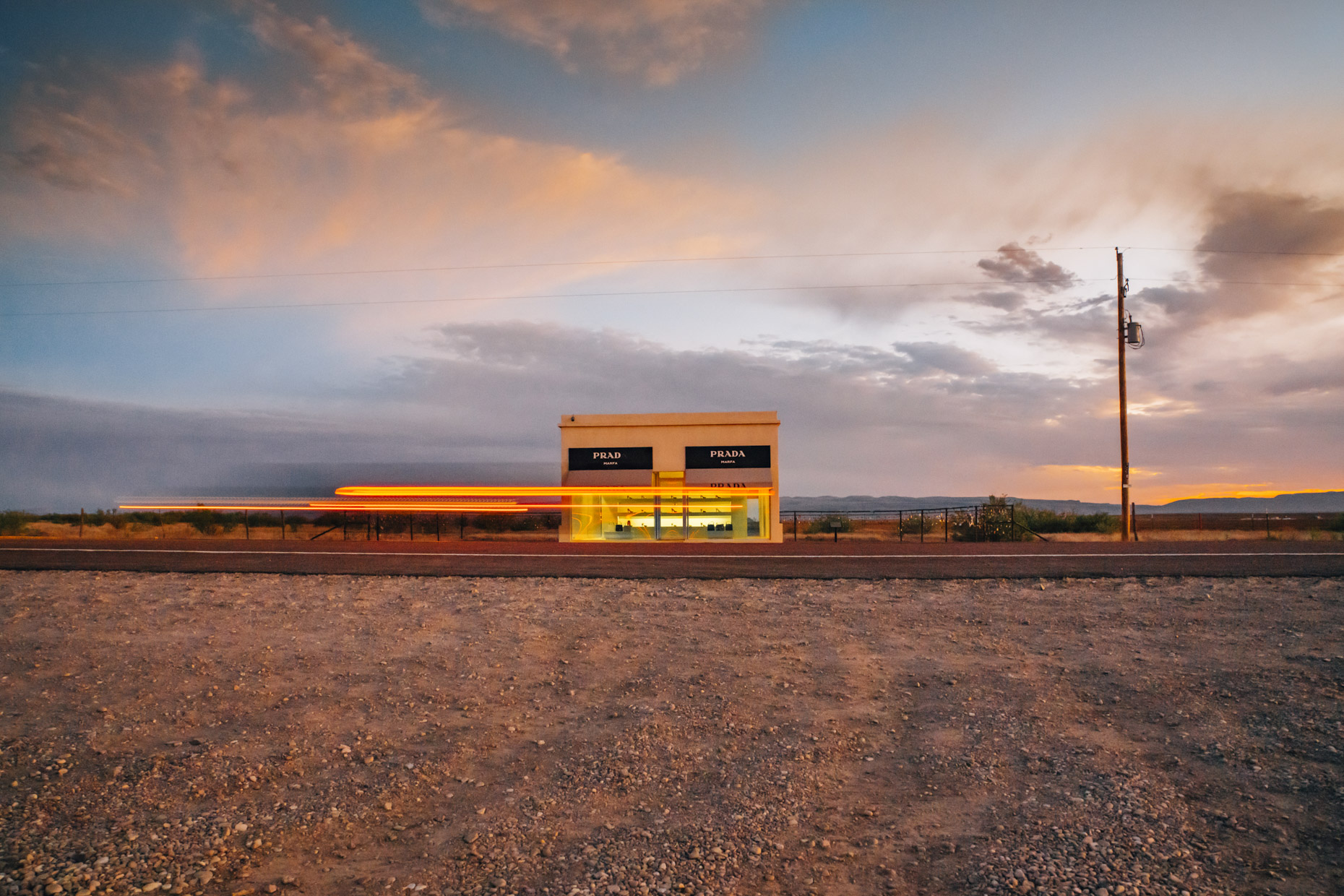 Prada store in Marfa, Texas at sunset with streak of car lights