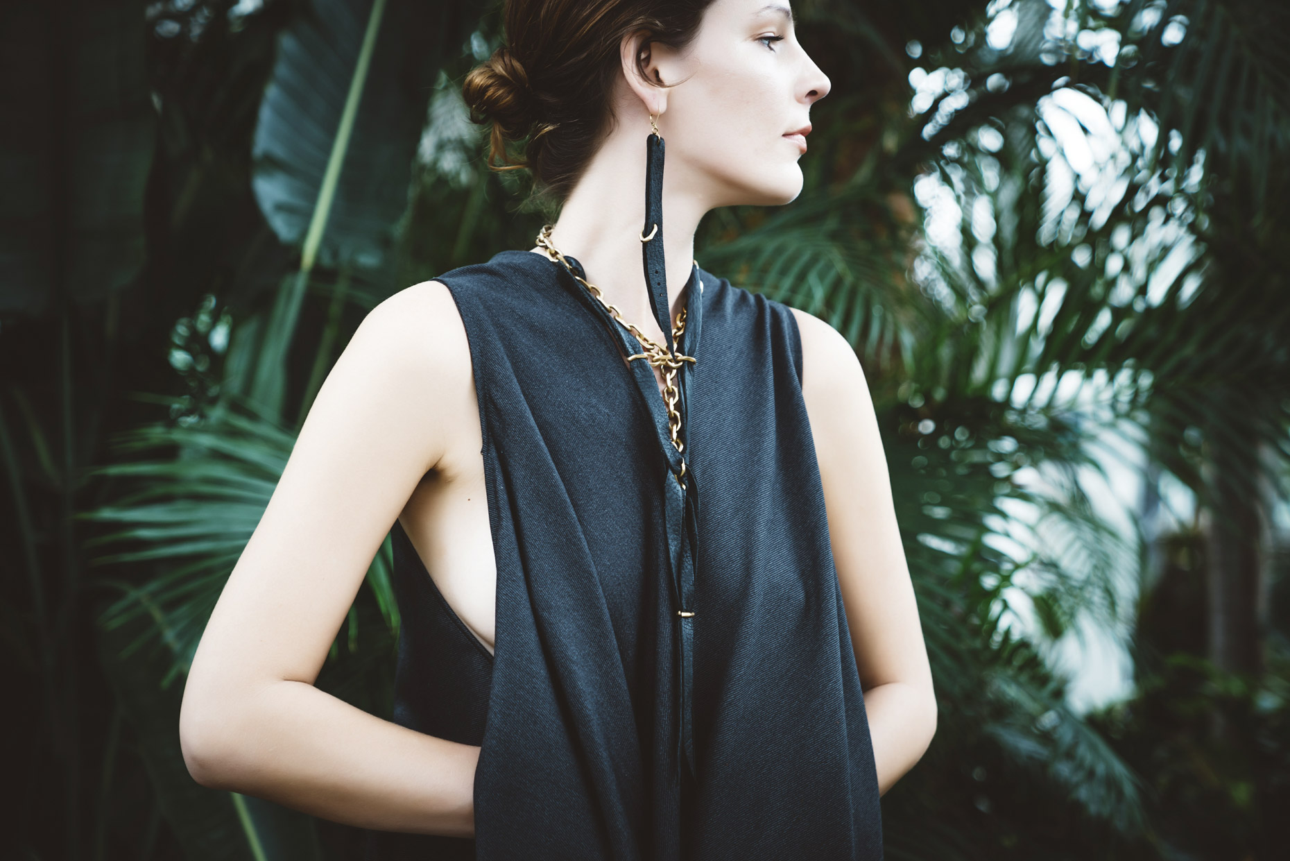 Profile of woman wearing black leather and brass necklace