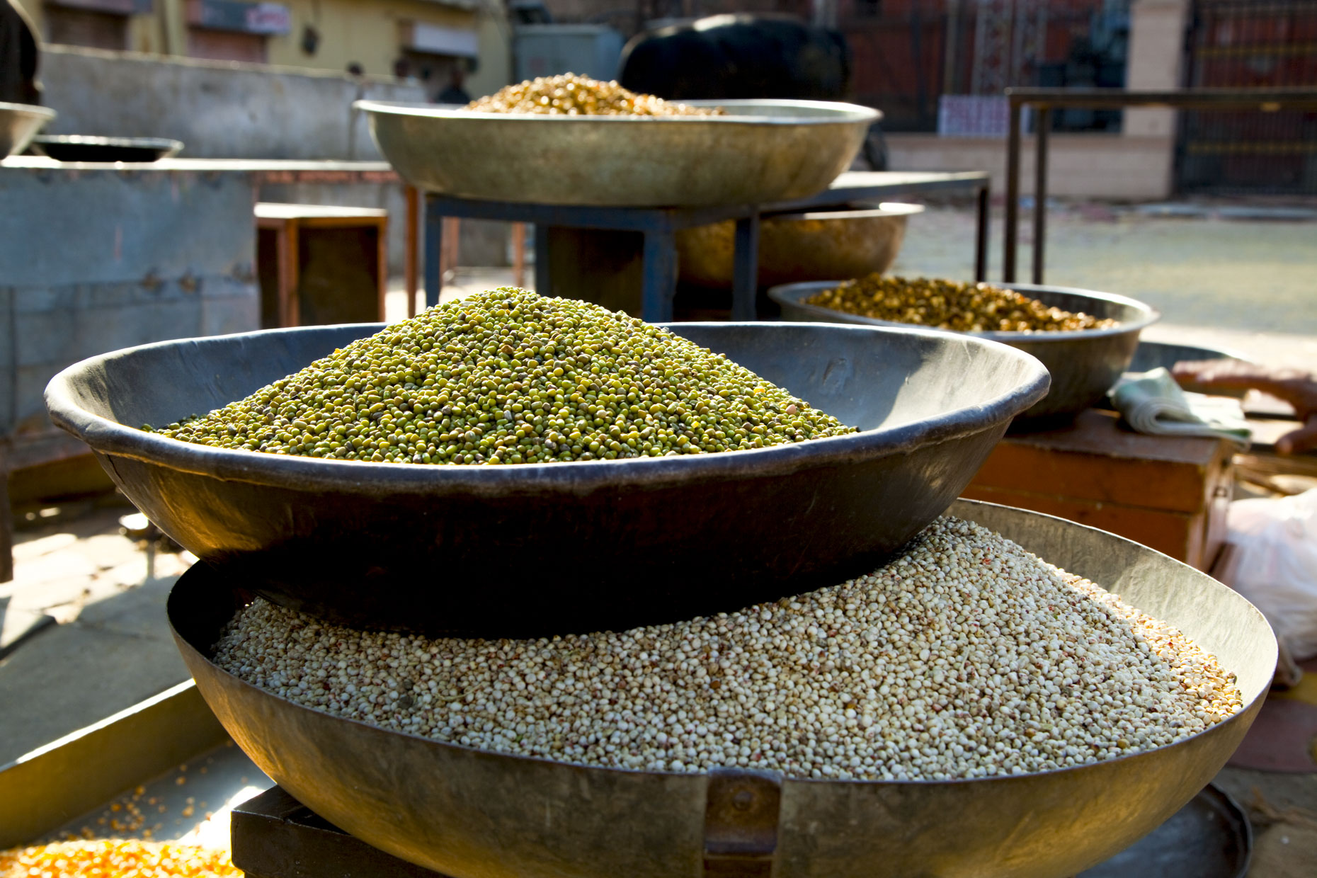 Lentils in brass bowls in outdoor market in Rajasthan India. Travel editorial photo by Inti St Clair Austin Texas