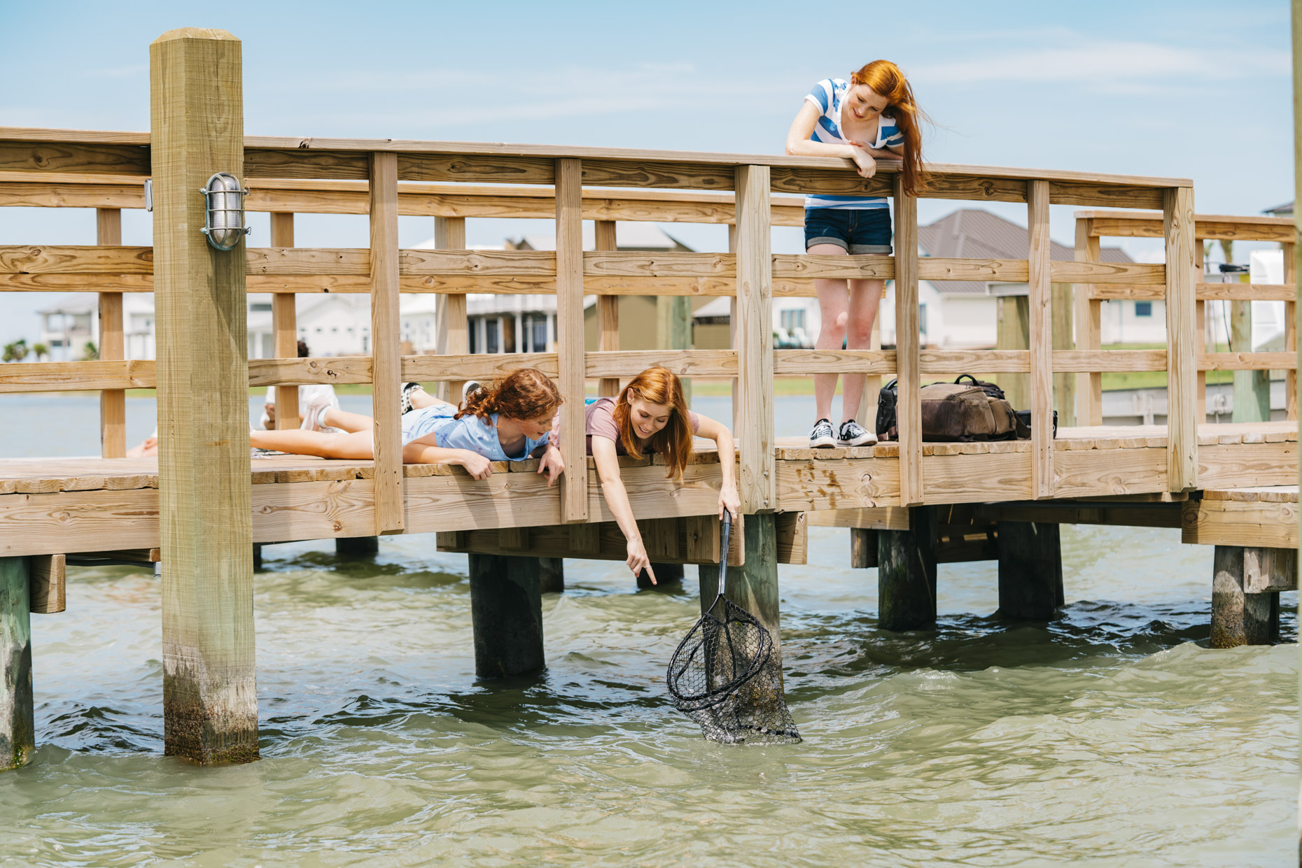 Red haired girls fishing with net from dock