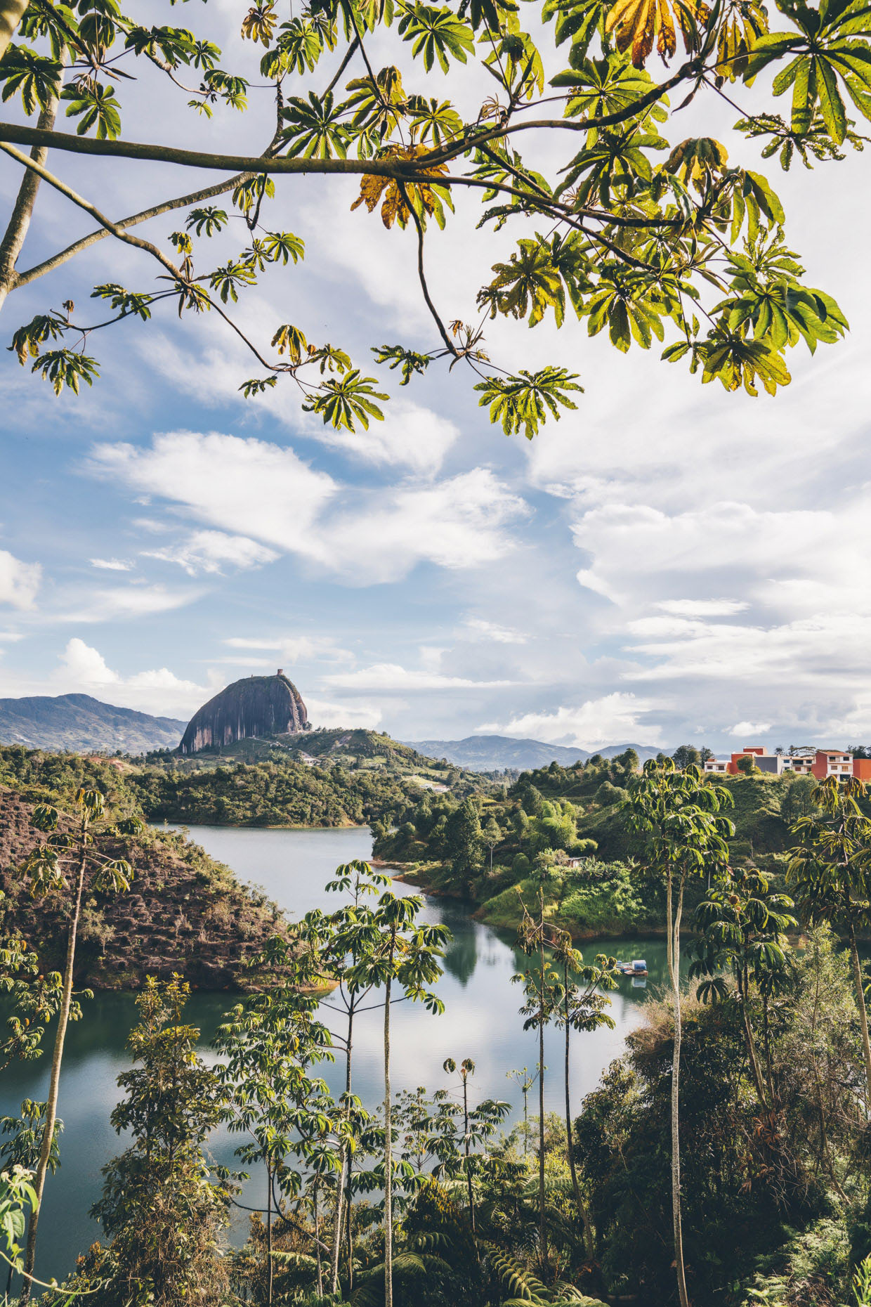 Rock of Guatape through tree leaves and across lake in Colombia