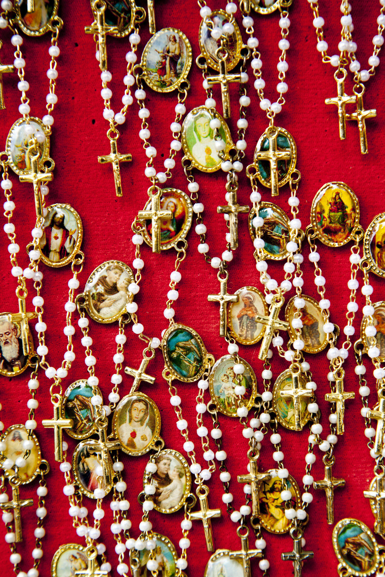 Tangle of rosaries on red cloth