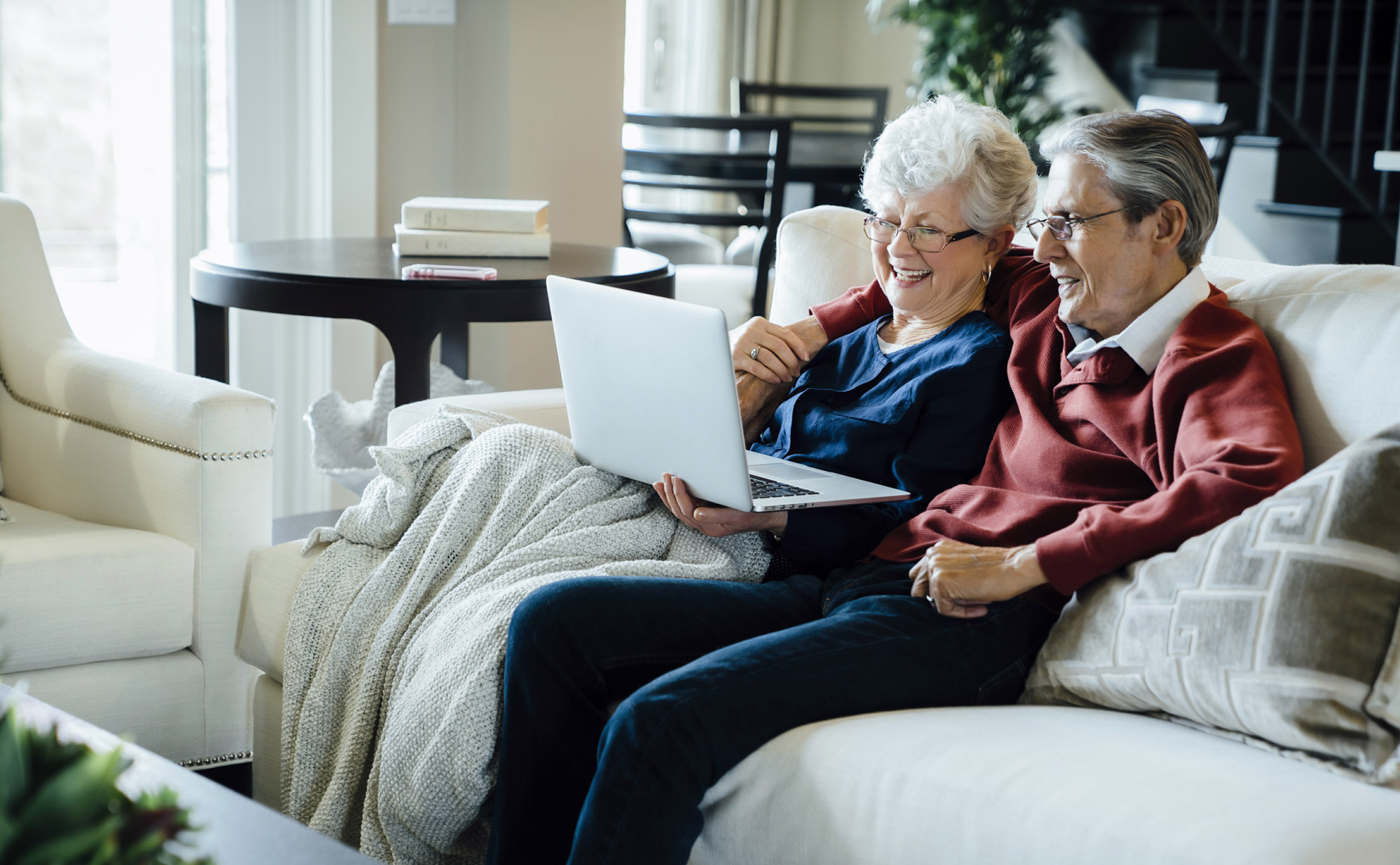 Senior couple snuggling on couch smiling at laptop