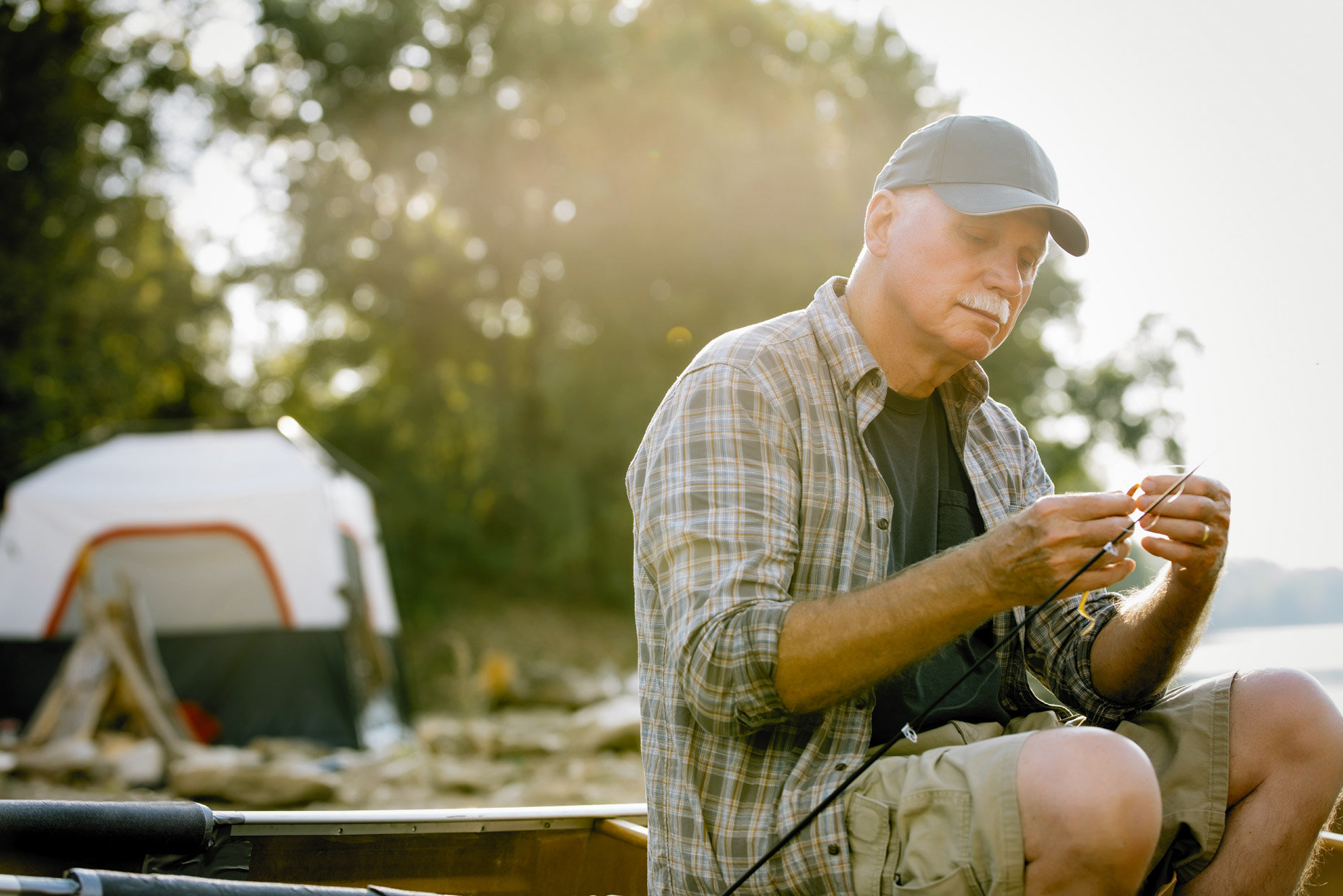 Senior man fishing by camping tent